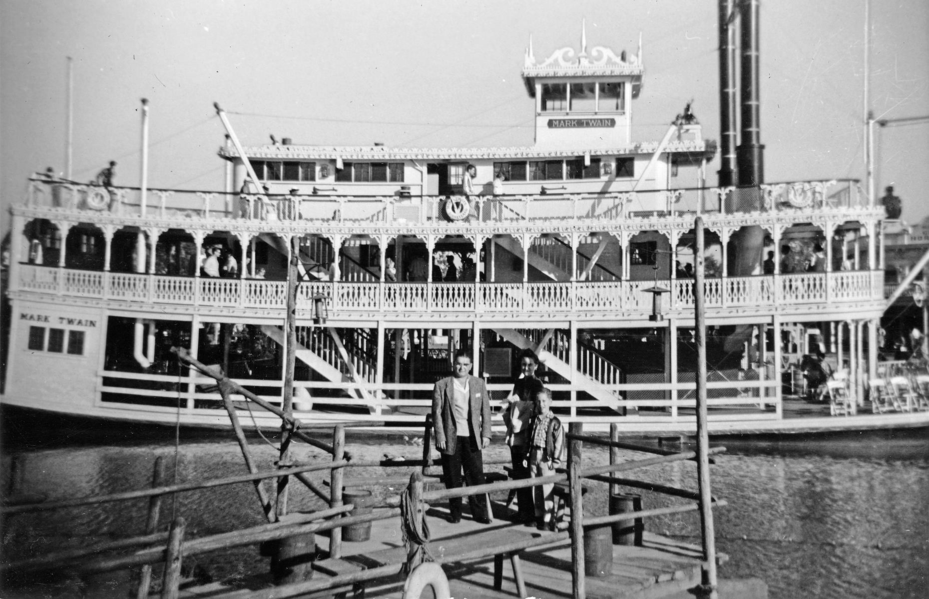 Slide 10 of 38: Another of Frontierland's early attractions was the Mark Twain Riverboat, which still plows Disneyland Park's rivers today. Here the paddleboat, named for the celebrated American writer, is seen from Tom Sawyer Island in 1956. The island, inspired by Twain's The Adventures of Tom Sawyer, still remains today too.