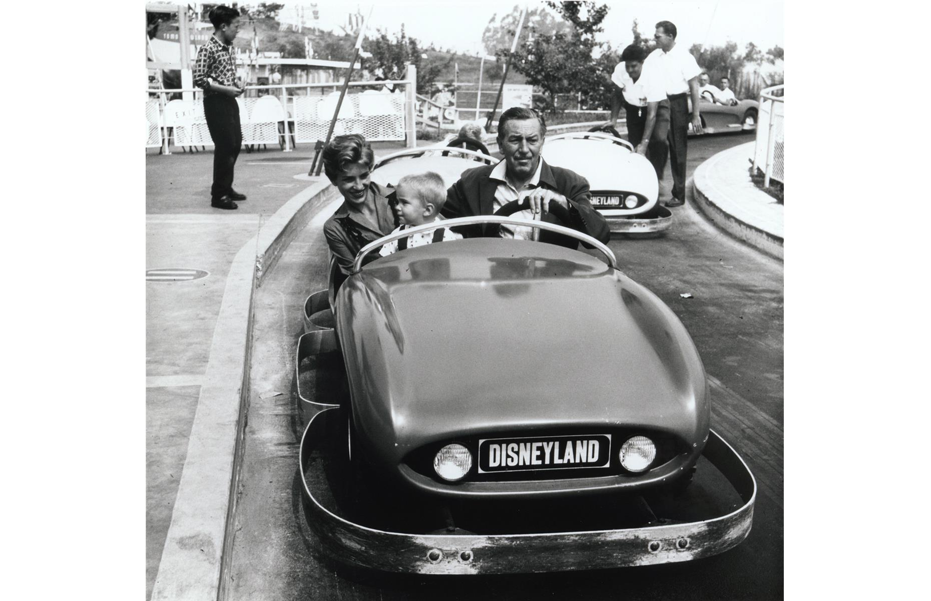 Slide 13 of 38: Another vintage Disney family snap, this one shows the park creator with his grandson and his daughter too. They're whizzing around on Autopia, a miniature speedway that still exists today. It was one of the park's opening attractions, debuting in futuristic Tomorrowland, where it remains.