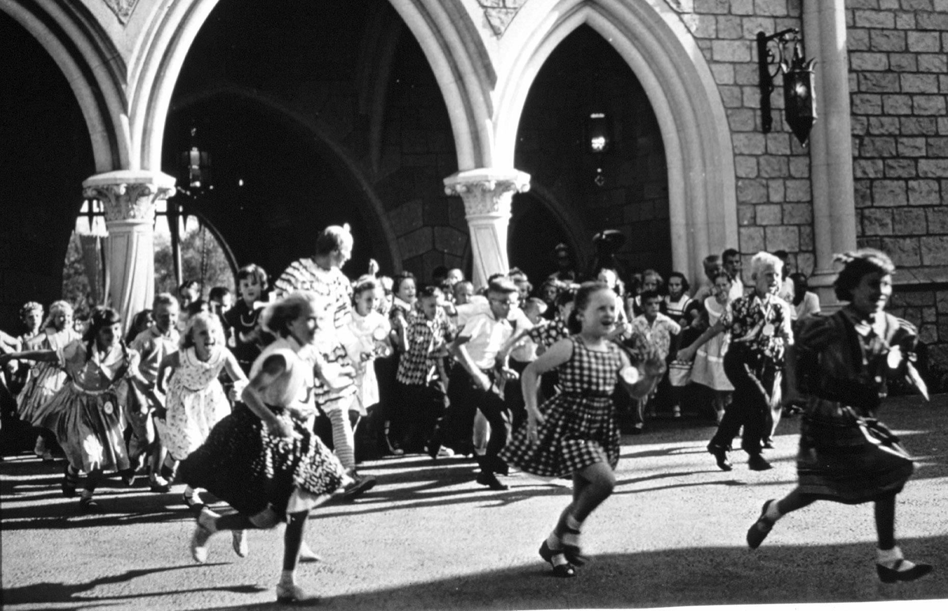 Slide 8 of 38: The park's youngest visitors could hardly wait to experience Disney's delights either. Here we see hundreds of excited children rush into the Fantasyland area of the park – the photo was taken immediately after the drawbridge entry was lowered on the opening day. The youngsters are headed straight for Sleeping Beauty Castle.