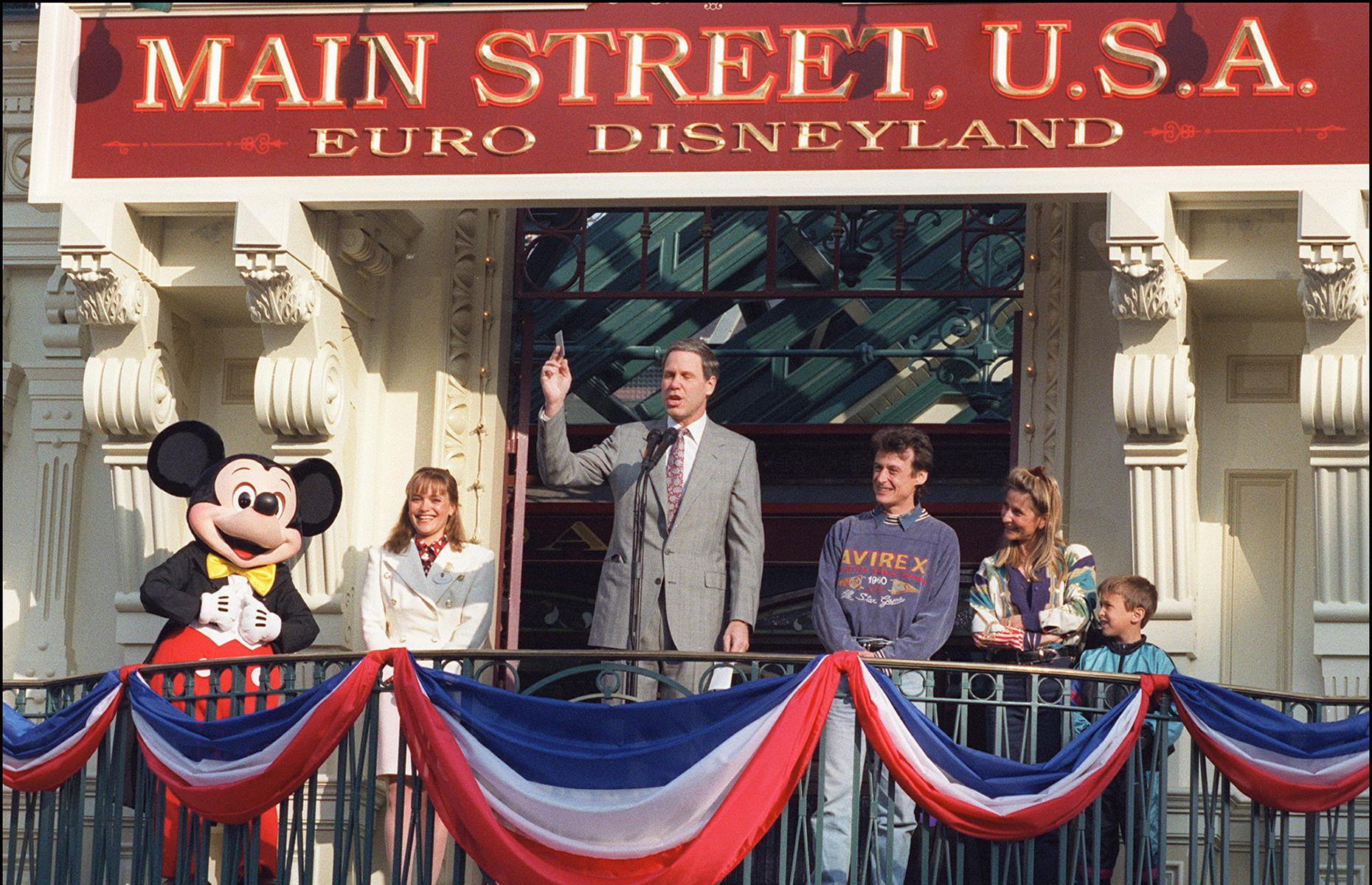 Slide 34 of 38: On the official opening day, then-chairman of the Walt Disney Company Michael Eisner gave a speech to an expectant crowd. Here he's seen at the entrance to Main Street, U.S.A holding up the very first entry ticket to the park. It's reported that the family who bought this ticket were granted free entry to the park for life.