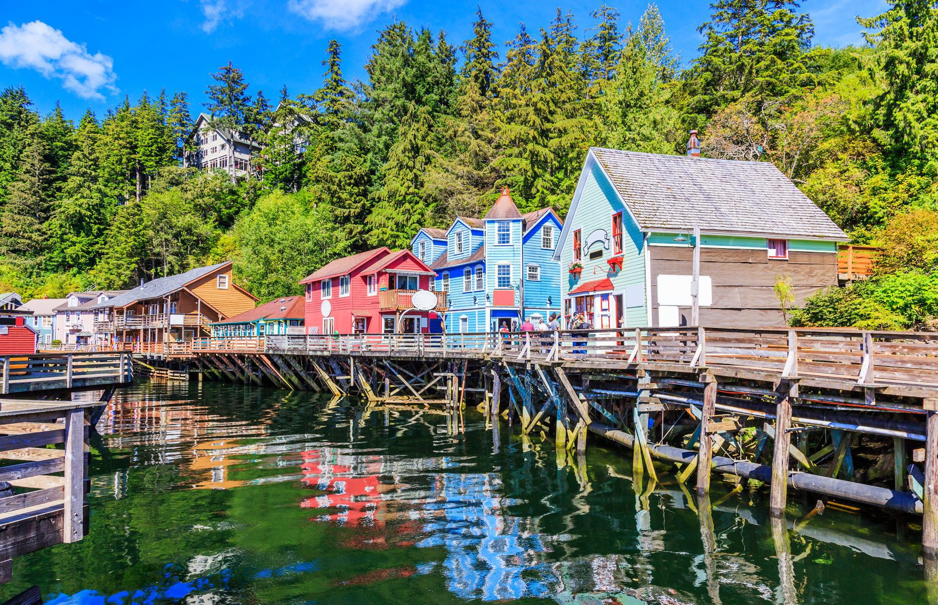 Slide 2 of 32: In the far south of the USA's most northerly state is Ketchikan, centered on a small cluster of colorful clapboard stilt houses perched over Ketchikan Creek. The city is known for its indigenous (mostly Tlingit and Haida) heritage and is the best place in the country to see intricately carved and brightly painted totem poles in their intended environment. And what an environment it is, with lush green forests, glacier-carved valleys and looming mountains just outside the city. Here's everything you need to know if you're traveling to Alaska from another state.