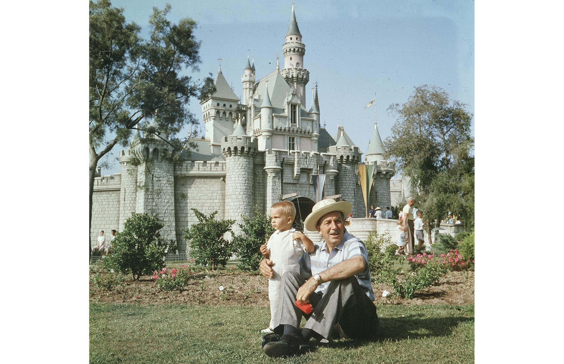 Slide 12 of 38: Disneyland was a family affair from the very beginning – and that included Walt Disney's own clan too. This heartwarming photo was snapped circa 1955, not long after the park's opening, and shows Disney with his little grandson on a grassy lawn before Sleeping Beauty Castle. You can spot other families in the background enjoying the majestic attraction too.