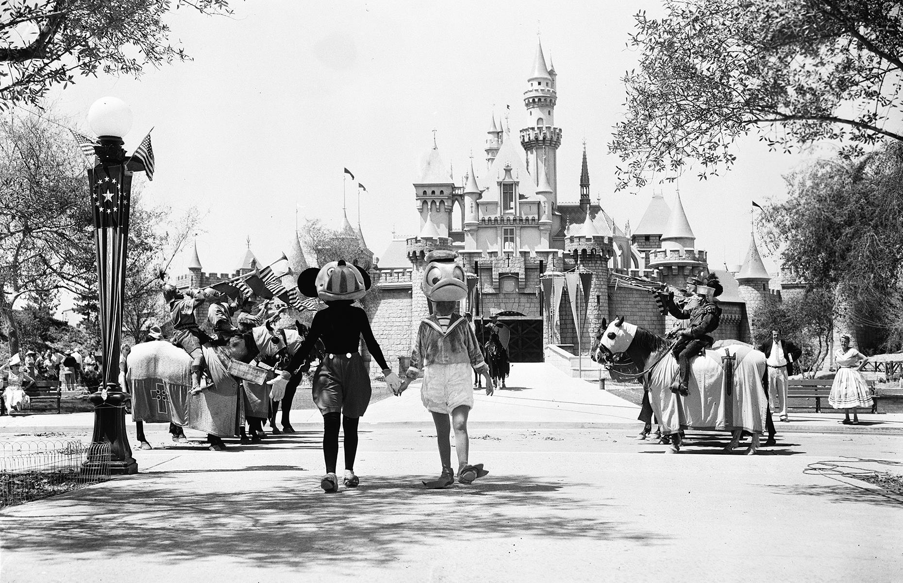 Slide 6 of 38: In renowned Disney fashion, the California park's opening was marked with loud, proud parades, music and appearances from familiar characters. Here Mickey Mouse and Donald Duck march out hand in hand before Sleeping Beauty Castle, as they're serenaded by fanfares from costumed folk on horseback.