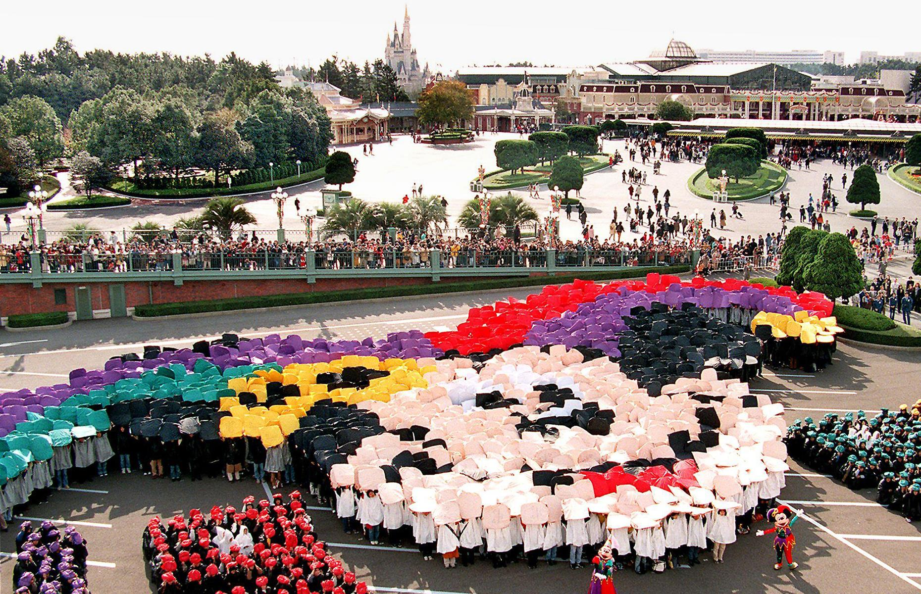 Slide 32 of 38: Some 15 years after its opening, in 1998, Tokyo Disneyland garnered world attention for the creative way it marked Mickey Mouse's 70th birthday. The celebratory spectacle involved more than 2,000 people holding colorful materials above their heads to form an image of Mickey's beaming face.