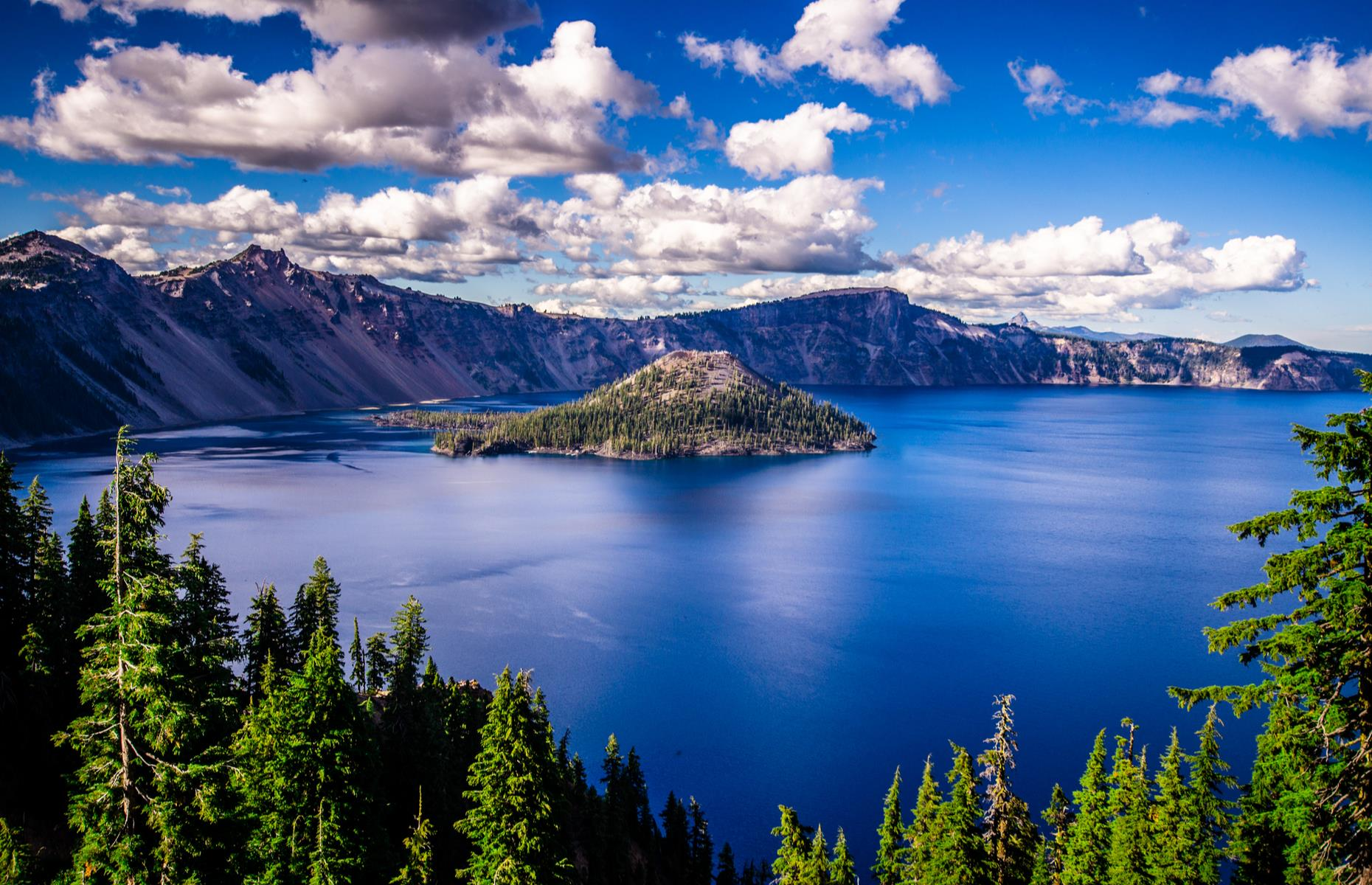 Slide 88 of 100: One of the deepest lakes in the world – and the very deepest in the United States – Oregon's Crater lake was formed some 7,700 years ago, when a volcanic peak collapsed, leaving behind a vast caldera. It plunges to a depth of 1,943 feet (592m) and its vivid sapphire waters are ringed by mountains and old-growth forest.