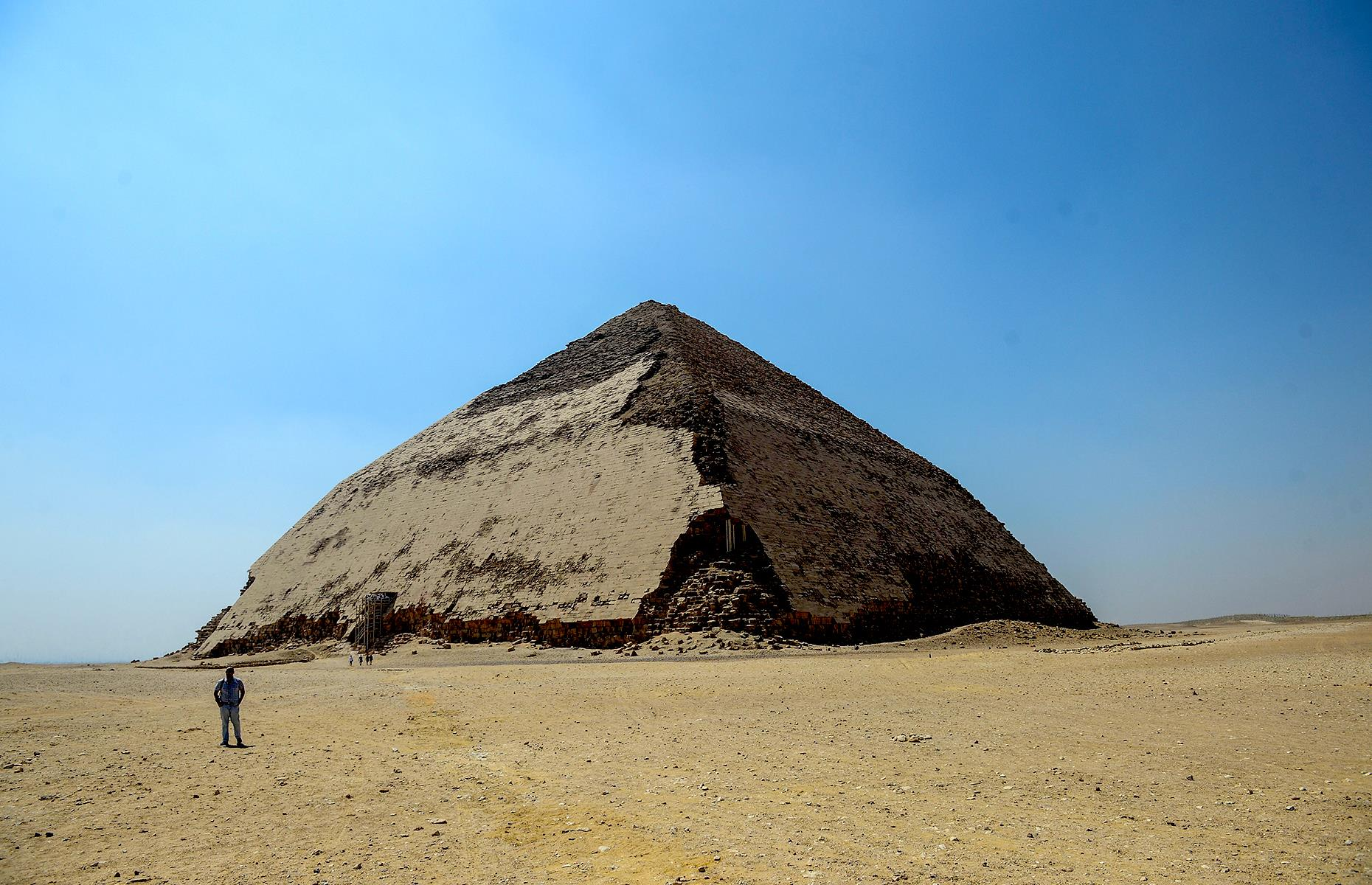 Slide 4 of 50: It might not be the most famous of Egypt's pyramids, but this striking structure in Dahshur still has secrets aplenty. Reopened to the public in 2019 for the first time since the 1960s, the Bent Pyramid (so named for its curious shape) sits around 25 miles (40km) south of capital Cairo. It's thought to be around 4,600 years old, dating back to 2,600 BC, when it was built for the pharaoh Sneferu. But despite its many millennia, its riches are only just being discovered.