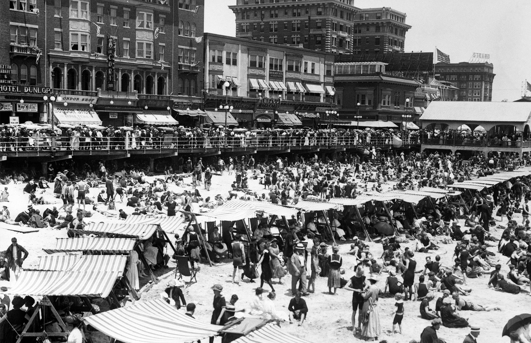 Slide 4 of 47: The beach was – and is – as much of a draw as the boardwalk, especially during sticky summers. Here, in the Roaring Twenties, sun-seekers bask on the sand or cool off beneath striped shelters, as the famed boardwalk bustles in the background.