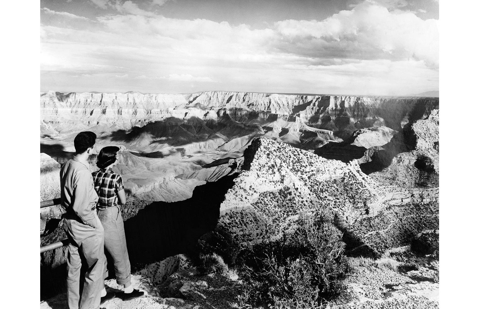 Slide 9 of 47: Today the canyon is peppered with scenic viewpoints, from the famous glass Skywalk at the West Rim to Mather Point in the south. Here a couple in the 1940s stand at a rugged observation point and drink in the otherworldly landscape.