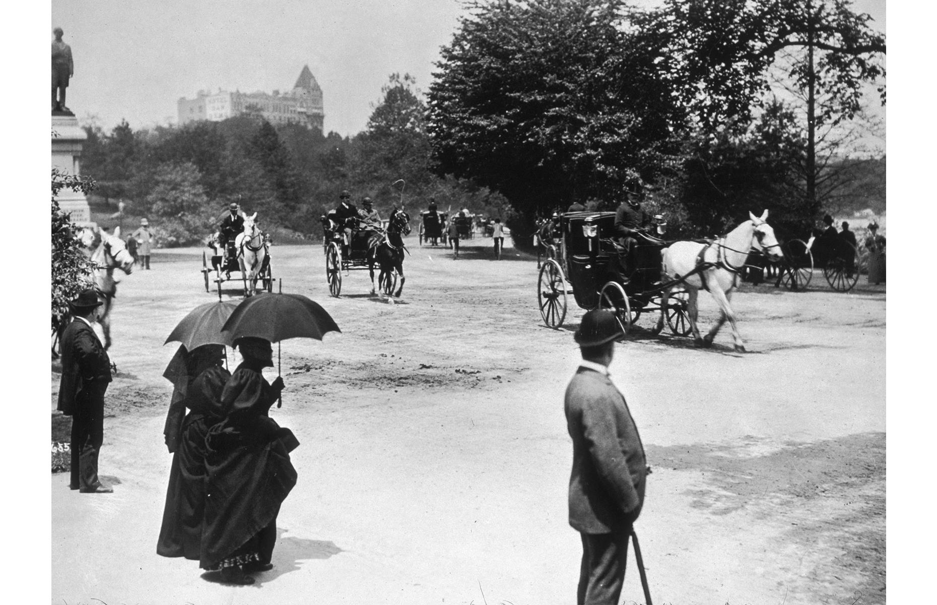 Slide 19 of 47: You can still take a carriage ride through Central Park, but back in the 19th century, the sight of tourists bundled into a horse-drawn coach was even more common. Here, in 1899, pedestrians watch on as gentle steeds clip-clop their way through the park. They're standing on the Mall, a pathway purposefully built to accommodate carriages.