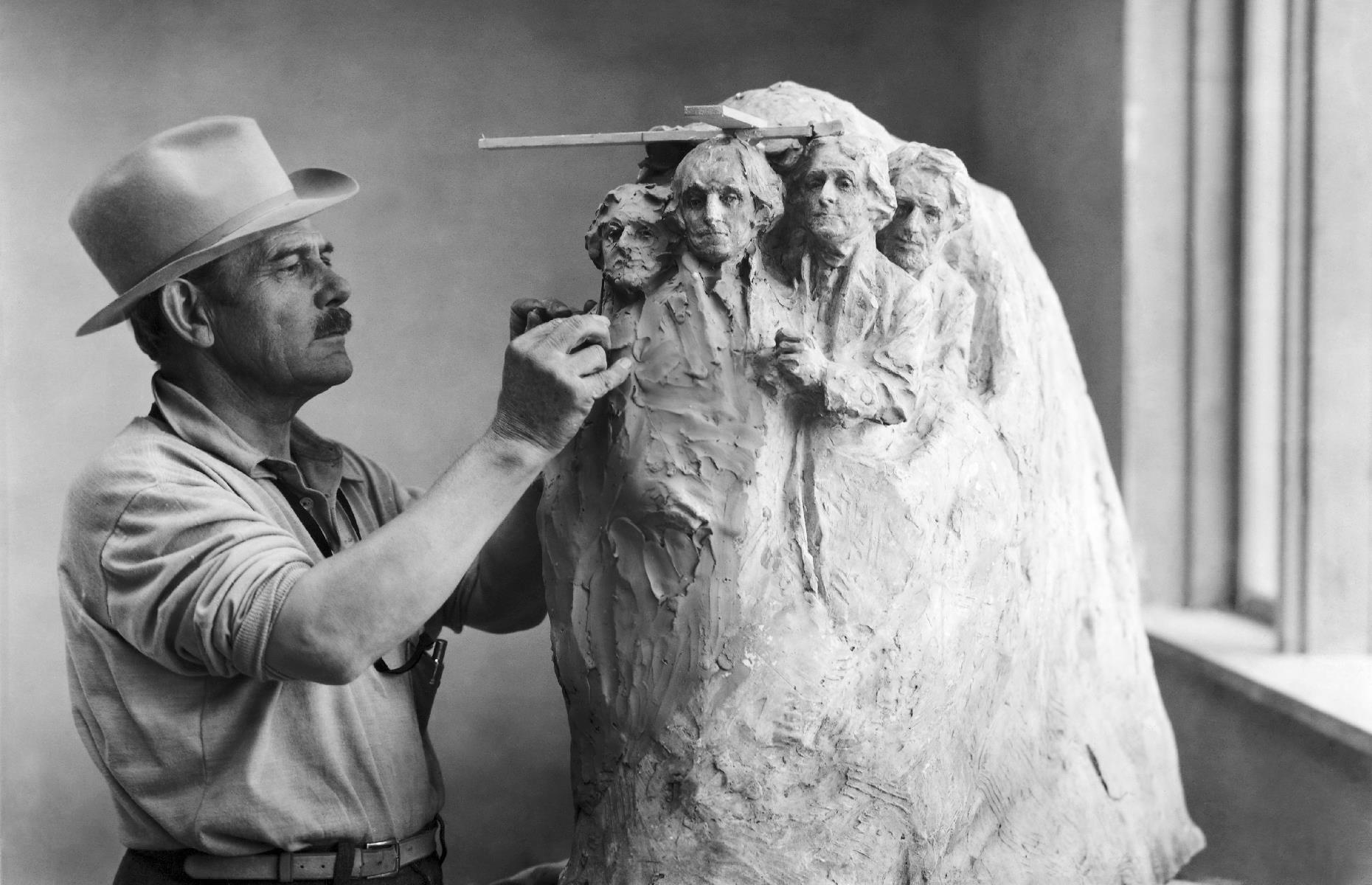 Slide 41 of 47: The four stone presidents of Mount Rushmore –George Washington, Thomas Jefferson, Theodore Roosevelt and Abraham Lincoln – have been watching over South Dakota's Black Hills region since they were completed in 1941. Here we see lauded sculptor Gutzon Borglum in his studio, working on the design for what would become one of America's most iconic attractions.