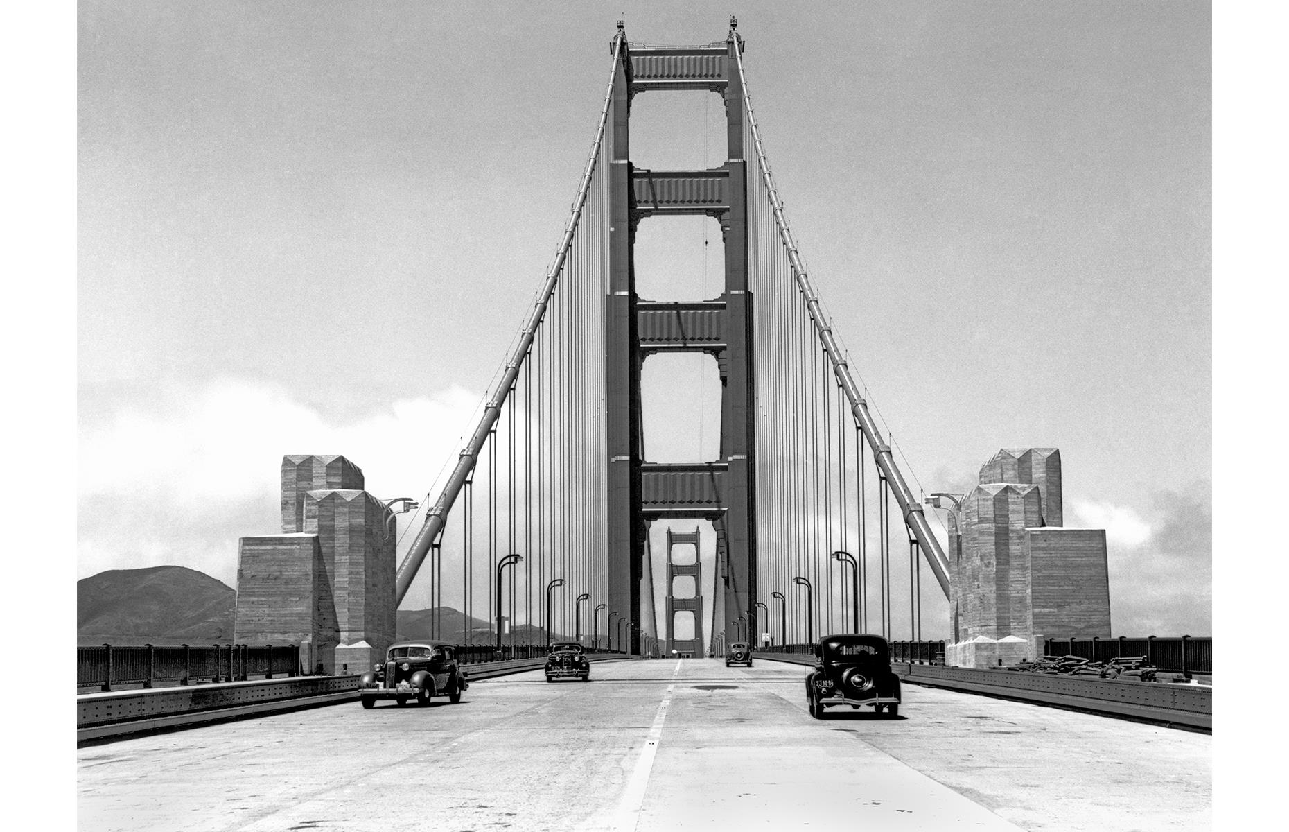 Slide 44 of 47: The epic bridge was eventually completed in 1937, and opened to traffic in May of that same year. Journalists were among the first to take a drive across the mammoth expanse – a handful of press cars are pictured here on 24 May 1937, a few days before the structure's official opening date.