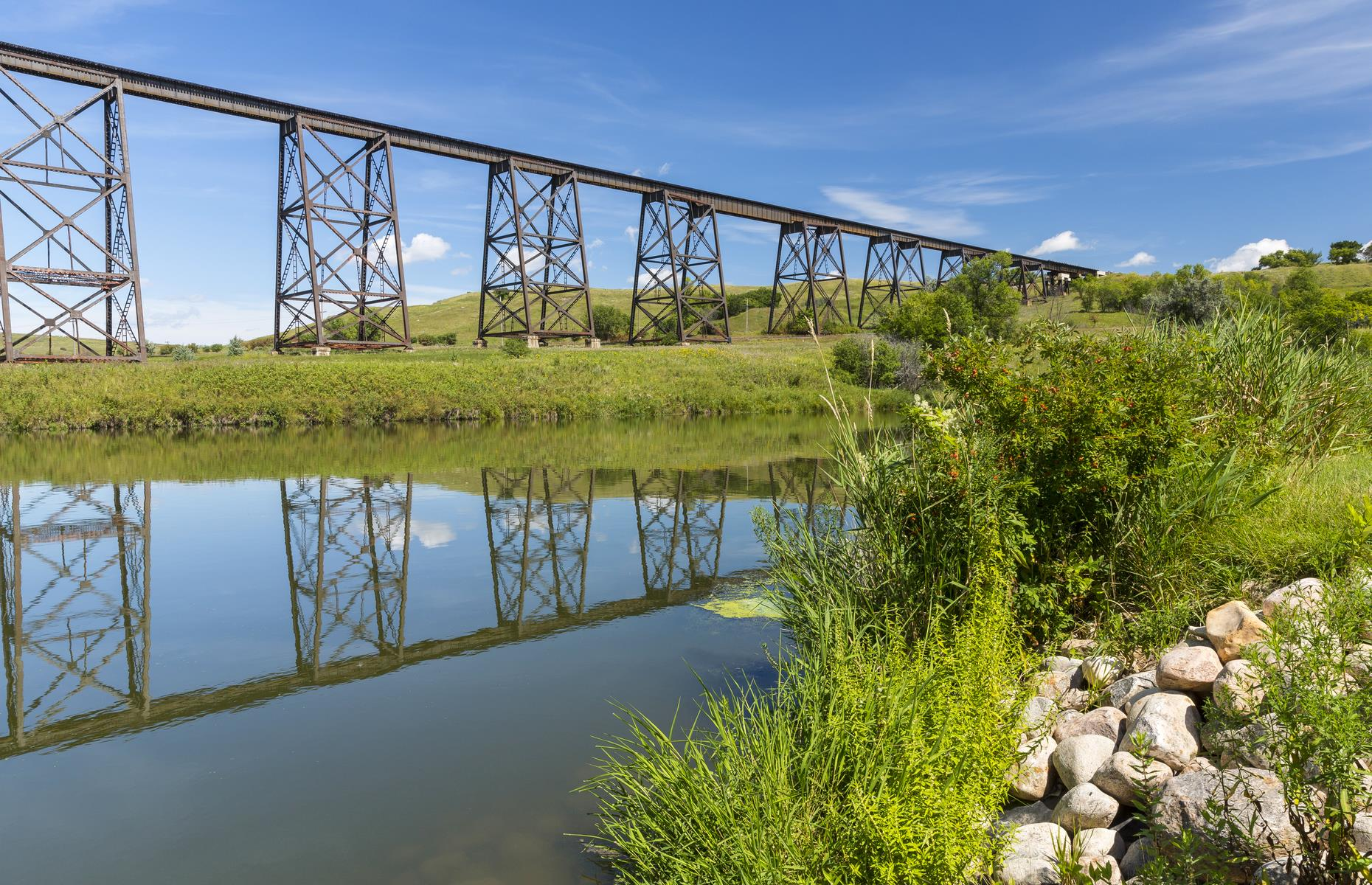 Slide 36 of 52: This historic railroad bridge could have been pulled straight from an old Western movie. It was completed more than a hundred years ago, in 1908, and beats an unswerving path across the Sheyenne River in Valley City. Held up to its 162-foot (49m) height by 30 hardy towers, the bridge was pivotal in the Second World War as supplies and soldiers were transported over the river in coast-to-coast journeys. It was closely guarded during the entire conflict.
