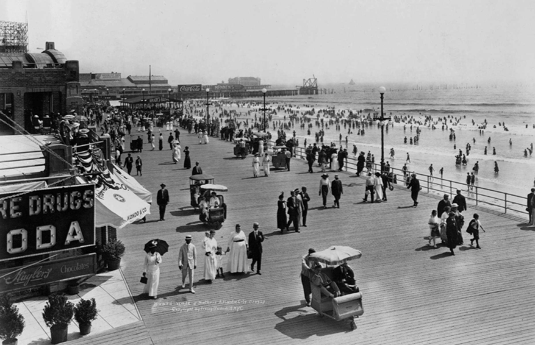 Slide 2 of 47: Atlantic City's beachside boardwalk has been a premier East Coast attraction since the 1870s, when the famous wooden pathway was first constructed. It's thought to be the first boardwalk of its kind in the United States, and has been lined with luxurious hotels, eclectic stores and restaurants since its earliest beginnings. Here vacationers wander the seaside boulevard on a sunny day in summer 1915.
