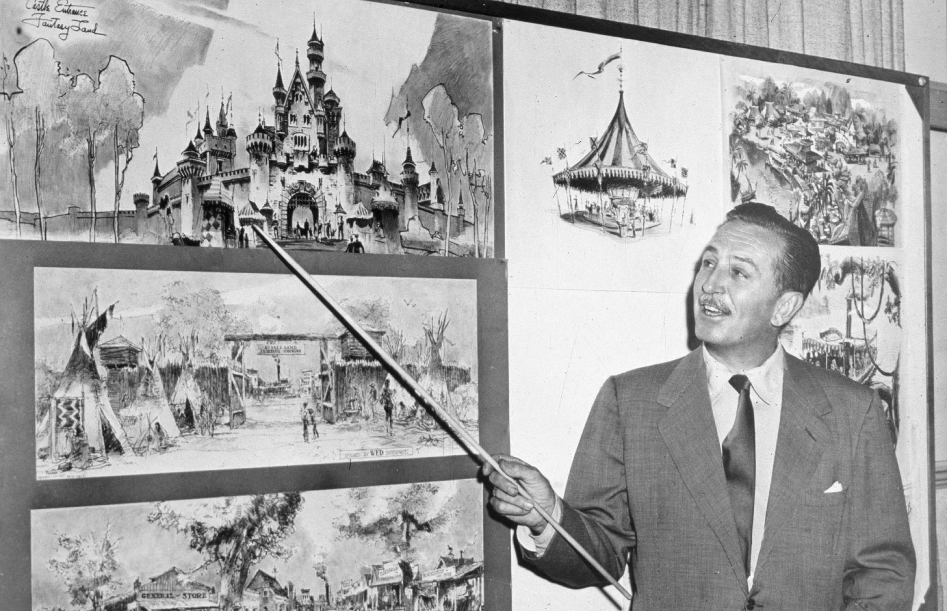 Slide 12 of 47: Though Florida's Disney parks have now dwarfed their Californian sisters in size, Disneyland in Anaheim will always be the oldest of these world-famous sites. It was, of course, dreamed up by animator extraordinaire Walt Disney himself, who was inspired by parks and attractions around the world. He's seen here with park sketches in the 1950s – you can spot the towers and turrets of Sleeping Beauty Castle and the buildings of Frontierland in the bottom left.