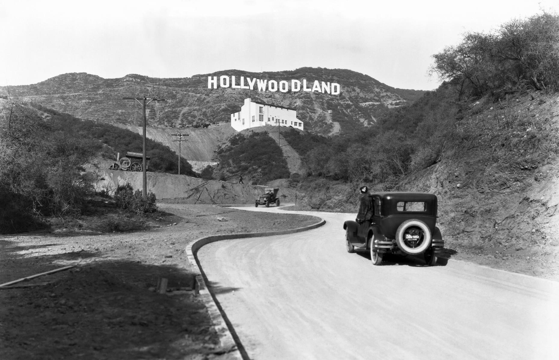 """Slide 47 of 47: The Hollywoodland sign stood tall for several decades, but eventually fell into disrepair. When it was finally fixed up in the 1940s, the """"land"""" section was ditched and the landmark we know today was born. It's pictured here around the mid-1920s, with white-washed Kanst Art Gallery rising up beneath it. Here's what to see in modern-day LA."""