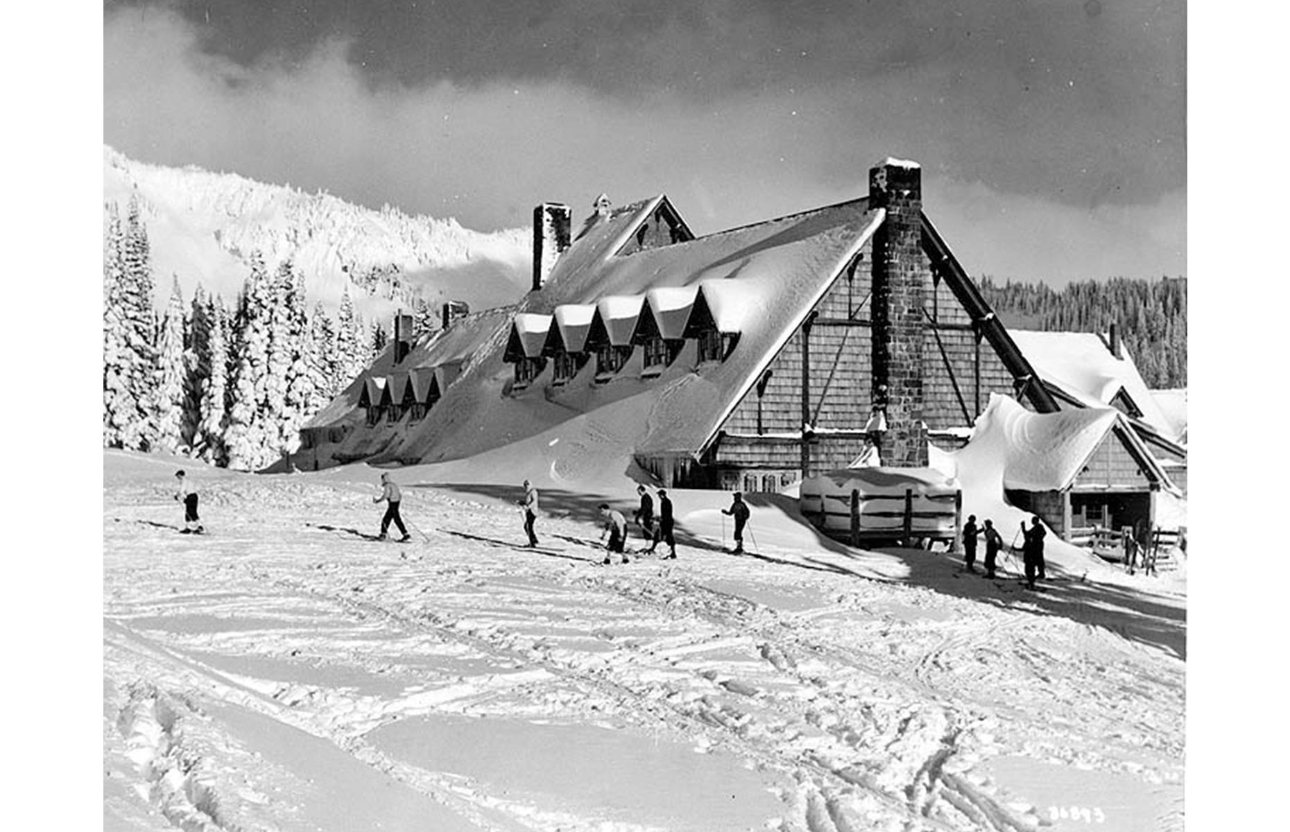 Slide 27 of 47: The Paradise area is still one of the most popular regions of the park today, known for its blossom-flecked meadows and its incredible opportunities for winter sports. Pictured here in mid-winter in the 1930s, skiers strike out from Paradise Inn, which is among the most well-loved lodges in the national park system. Dating to 1916, the inn makes for a dreamy winter retreat today, with its low beams, snug rooms and large fireplaces.