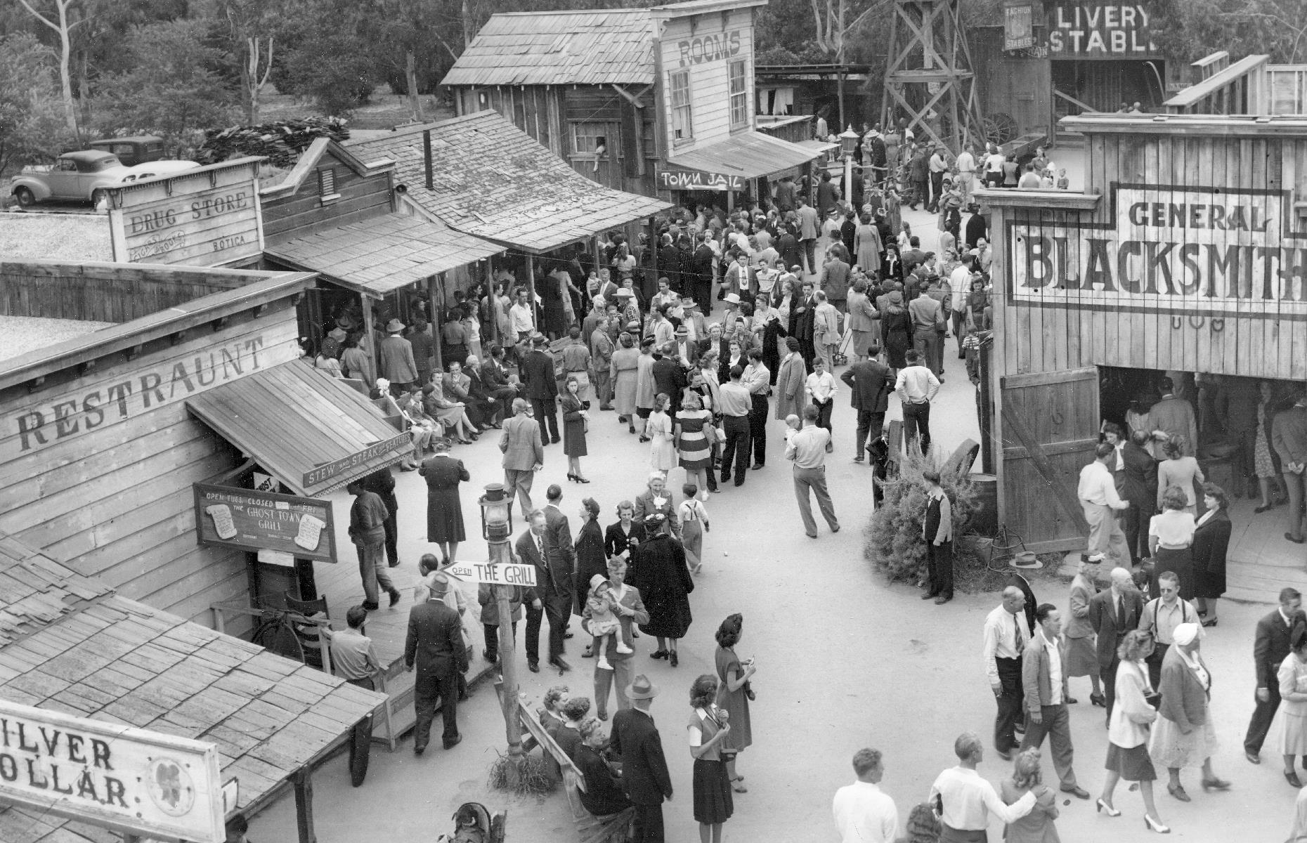Slide 32 of 47: Further visitors flooded in when Cordelia Knott began selling her delicious fried chicken dinner in the 1930s, and by the 1940s the pair decided to add yet more attractions. The Ghost Town, an Old West-themed area packed with wooden buildings from a blacksmiths' shop to saloons, opened in this decade. It's pictured here crammed with visitors in its early days.