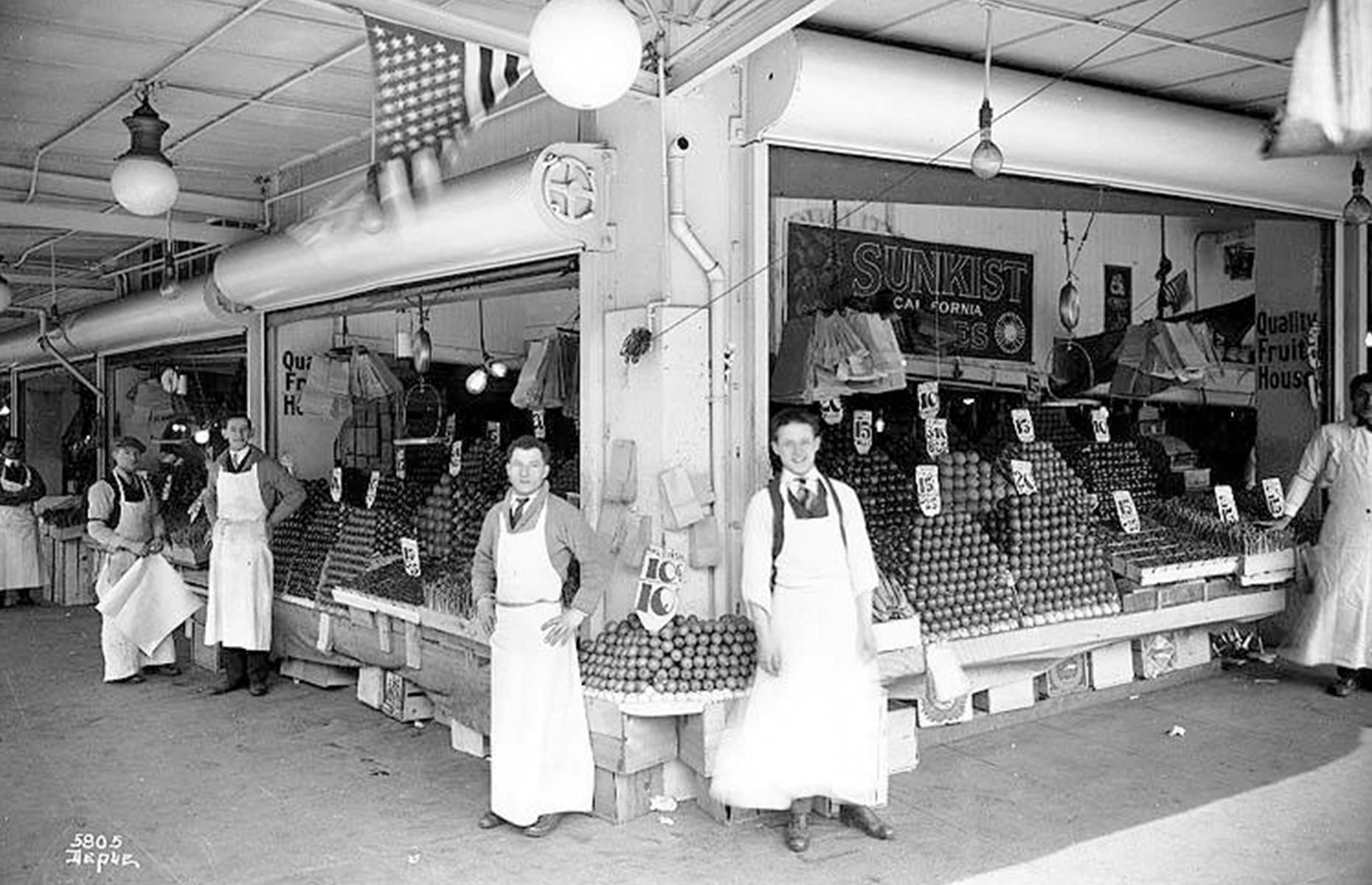 Slide 36 of 47: The first permanent building was constructed later in 1907, housing 76 produce stalls, which heaved under the weight of the season's fresh offerings –here vendors pose before their fruit stall in the 1920s. Today the produce stands are joined by craft stalls, indie boutiques and hip foodie spots too.