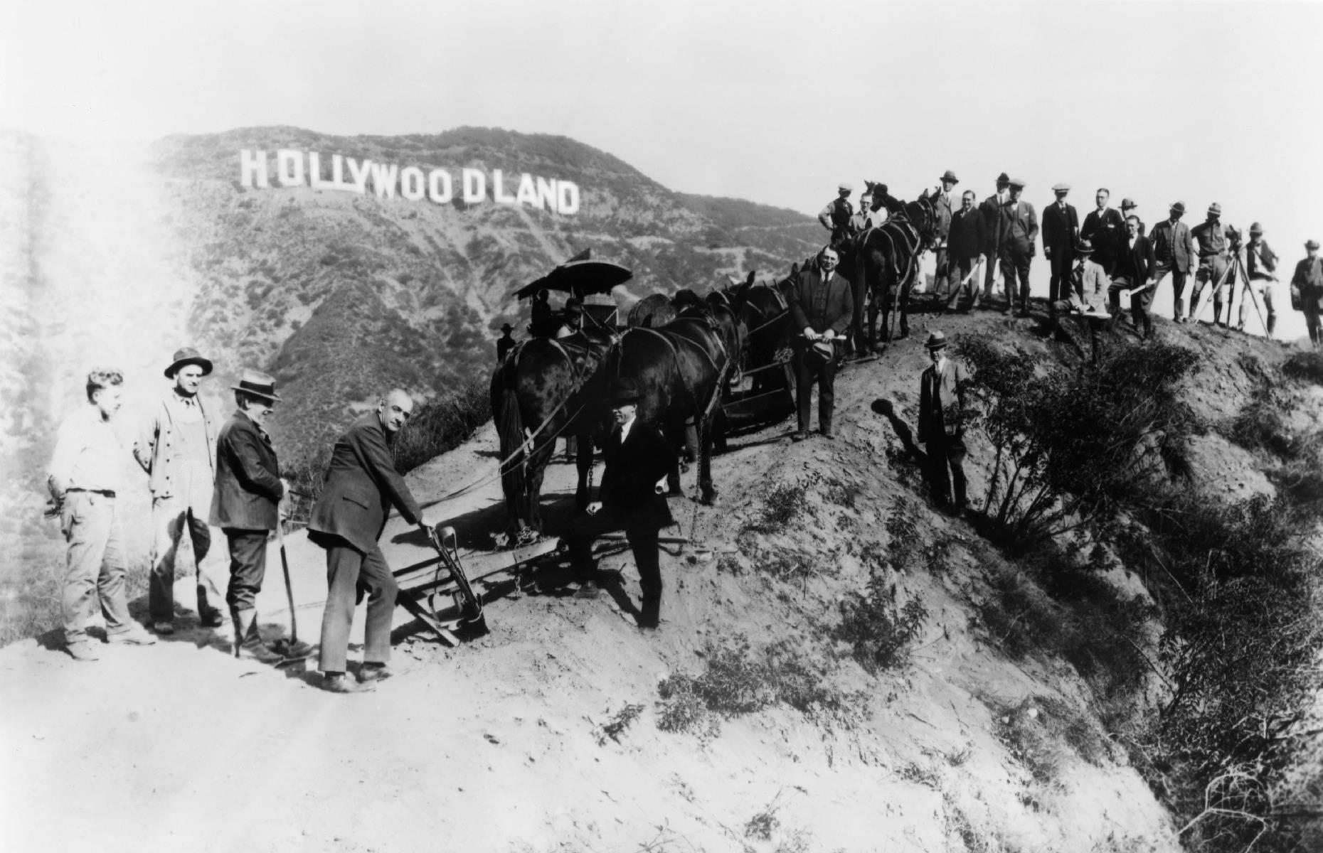 """Slide 46 of 47: The huge Hollywood Sign, standing high in the Hollywood Hills, is a familiar sight to tourists and Angelinos. It didn't always look as it does today, though. Originally an advert for a new housing development, it was erected in 1923 and read """"Hollywoodland"""". This photo shows a group of surveyors and builders for the new estate posing beneath the sign around 1925."""