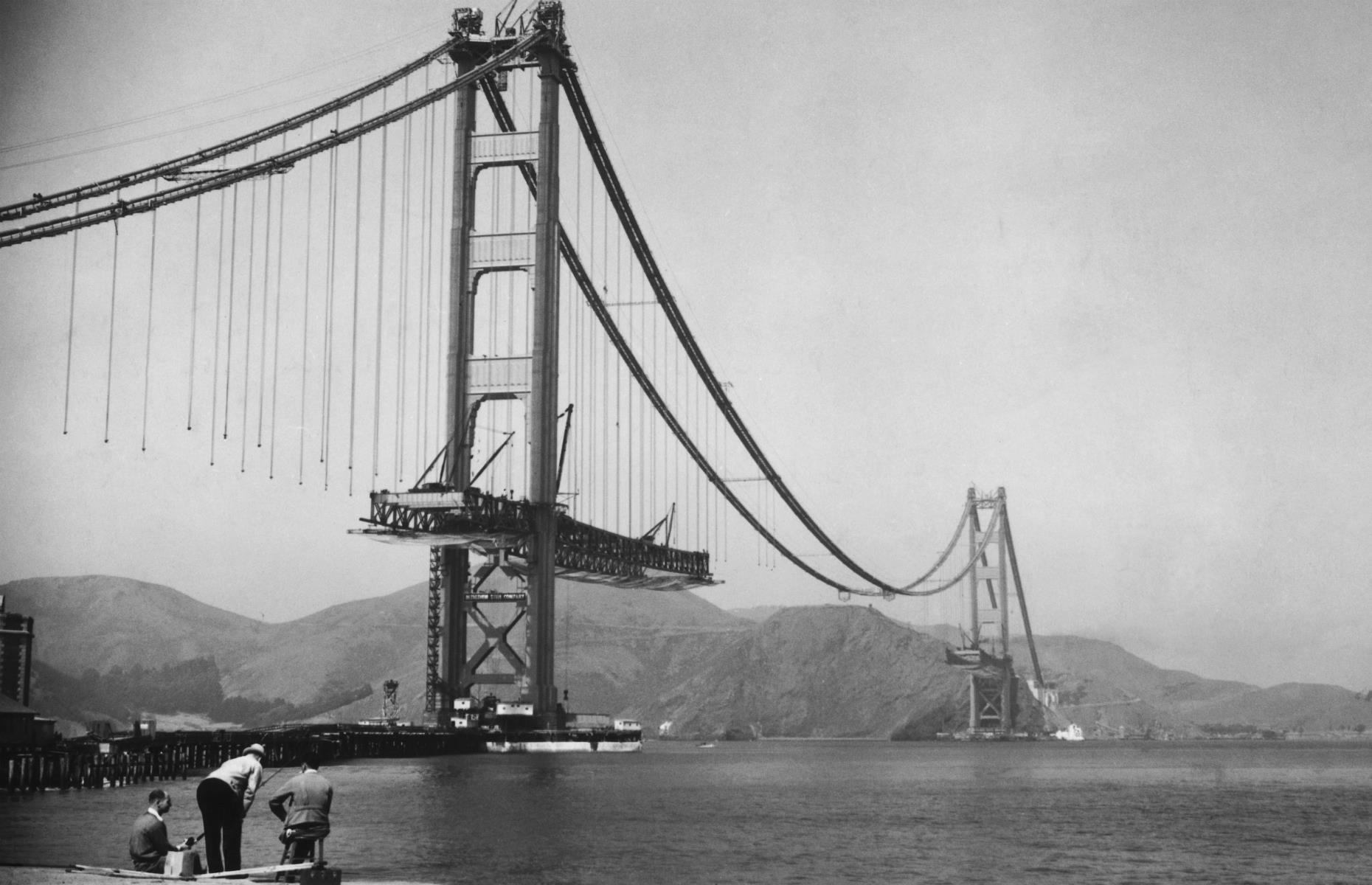 Slide 43 of 47: Arguably America's most famous bridge, the red-orange Golden Gate has spanned its namesake strait since 1937. When first completed, it was the longest and tallest suspension bridge on the planet, and its awesome size still wows modern visitors. The nascent bridge is pictured here in the mid-1930s, when its towers stood tall, but the main span was yet to be built.