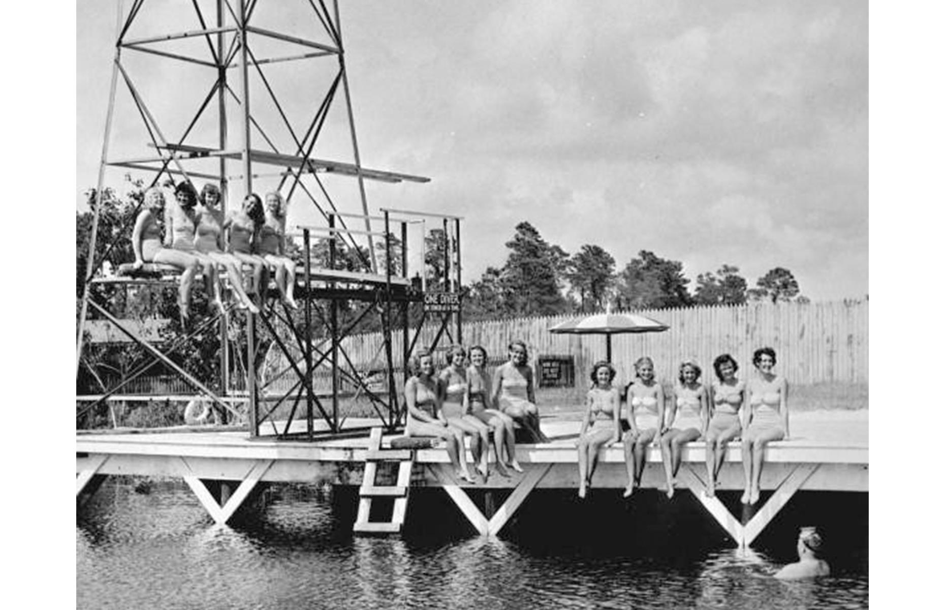 """Slide 38 of 47: To keep the magic alive, the mermaids rely on """"breathing hoses"""" invented in the 1940s by Newton Perry, the brains behind the attraction and its former owner. A troupe is pictured here in 1949, smiling from a dock and diving tower at Weeki Wachee, ready for their next show. The site now also boasts a water park, riverboat rides and casual restaurants."""