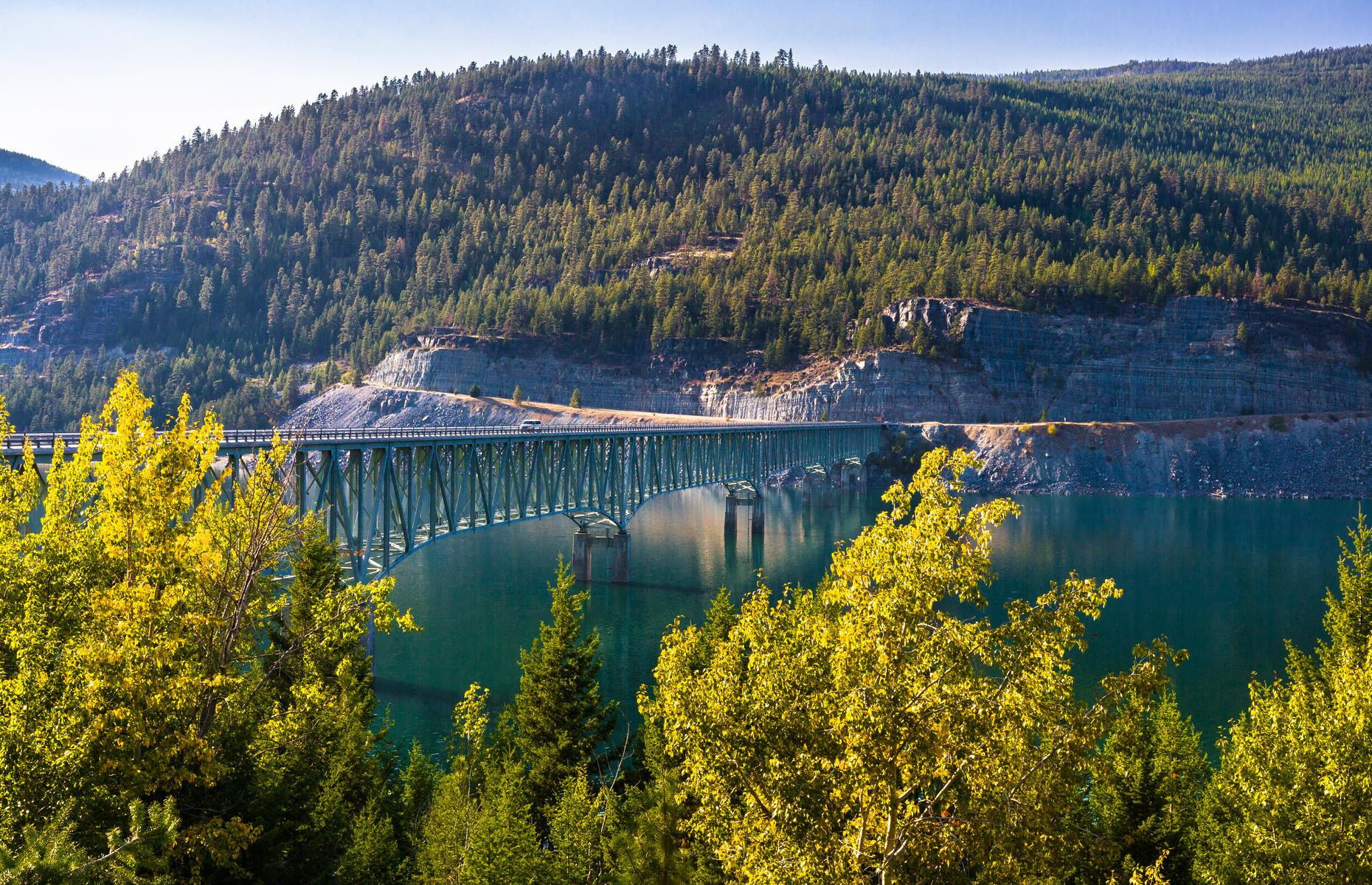 Slide 28 of 52: This bridge is the longest and tallest in Montana – but it's anything but imposing. Pale green in color, it's practically the same hue as glassy Lake Koocanusa which swirls below. It leads to the unspoiled Yaak Valley with its lush forestland and lakes.