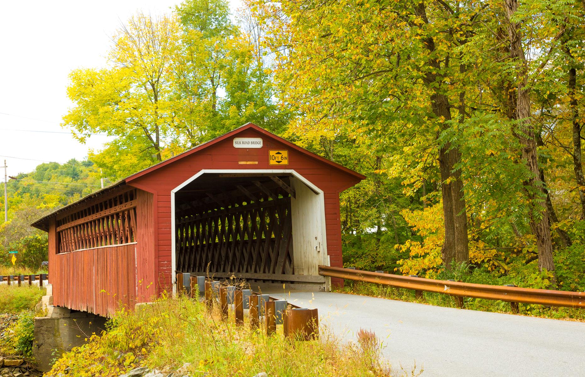 Slide 47 of 52: Vermont is another New England state famous for its covered bridges. This one has been straddling the Walloomsac River since the 1840s, spreading across 88 feet (27m) with intricate latticed detailing in its interior. In fall, its orange-red expanse blends beautifully with the surrounding foliage.