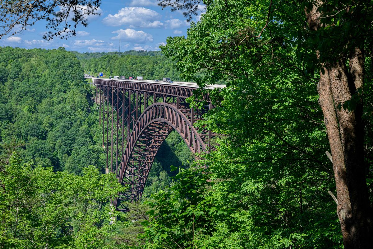 Slide 49 of 51: New River Gorge BridgeThe New River Gorge Bridge is a steel arch bridge that spans 3,030 feet long over the New River Gorge near Fayetteville, West Virginia. For 26 years, it was the world's longest single-span arch at 1,700 feet long, but now sits at the number four spot. Located in the Appalachian Mountains it defines taking the scenic route.