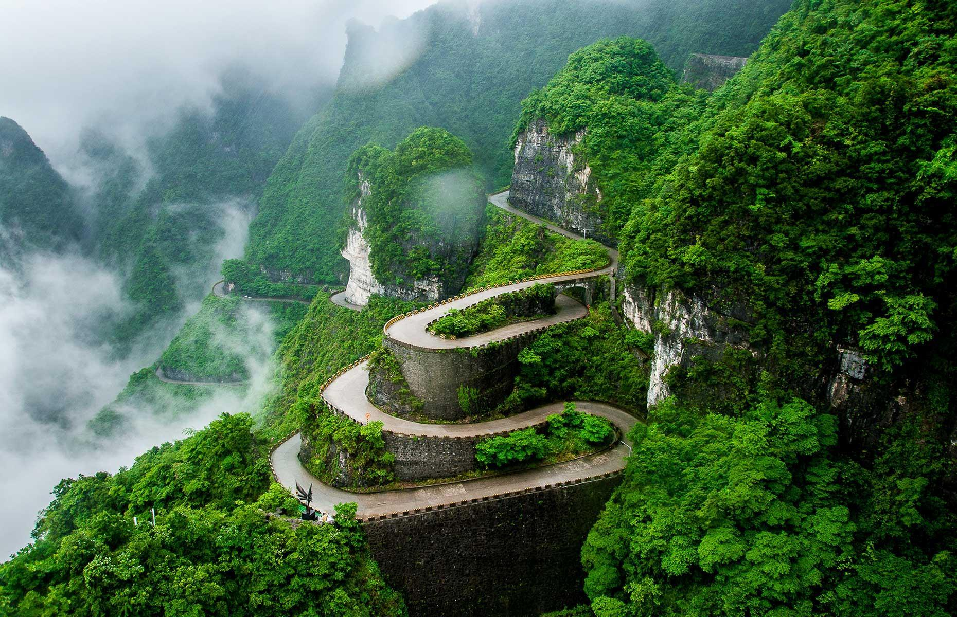 Slide 32 of 44: This spectacularly steep and winding road can be found in the Tianmen Mountain National Park in China's Hunan Province. It curls up the mountain for seven miles (11km) with 99 nerve-wracking bends and precipitous drops. The road ends at a natural gap near the mountain's peak. Although, you'll need to walk 999 steps after you've parked to reach the sacred crevice, which is known as Heaven's Door.