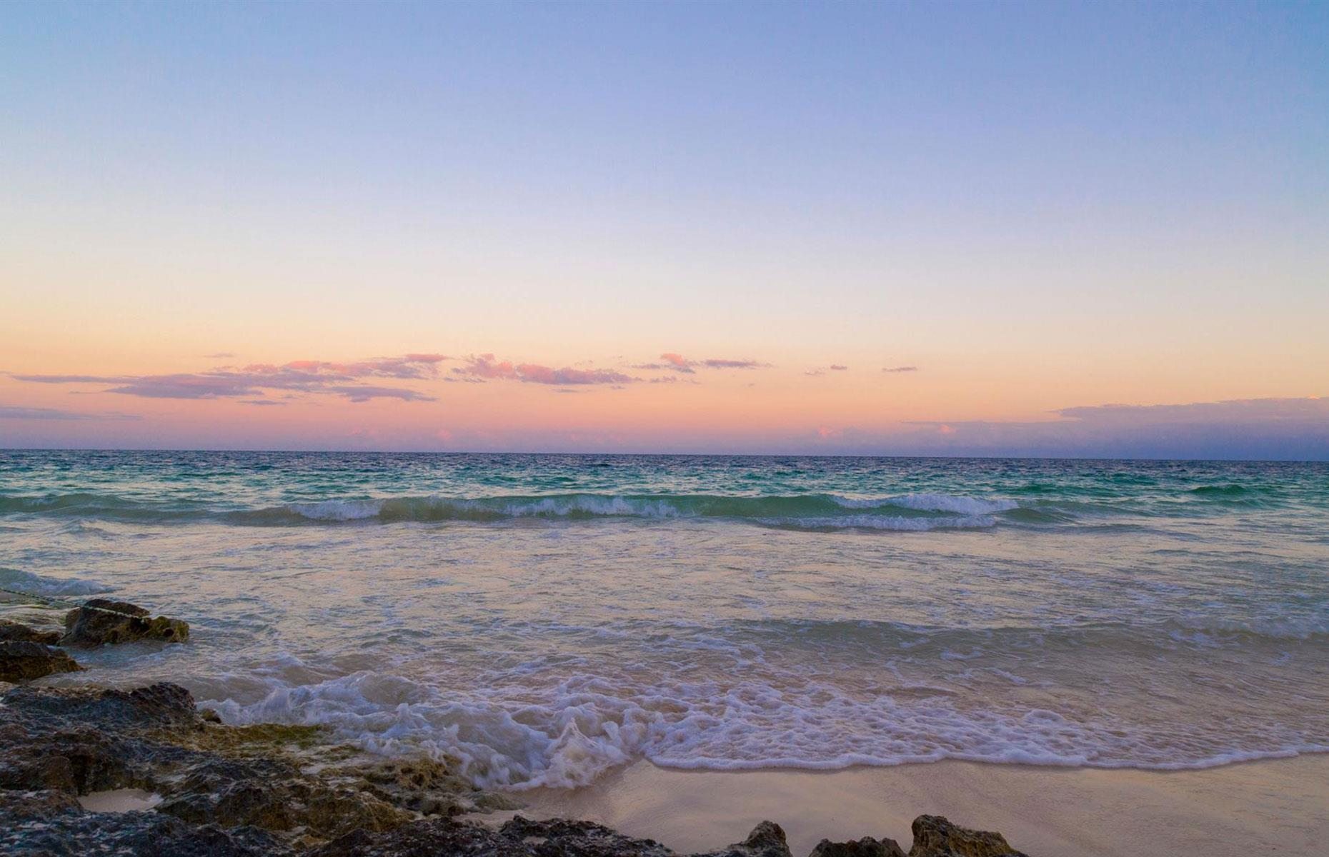 Slide 23 of 29: You don't always have to get on the same level as the clouds when looking for a magnificent sunrise. Tulum's 'paradise beach' in Mexico welcomes visitors with a spectacular coastal vista. The sun comes up at around 6am at mid-summer here.