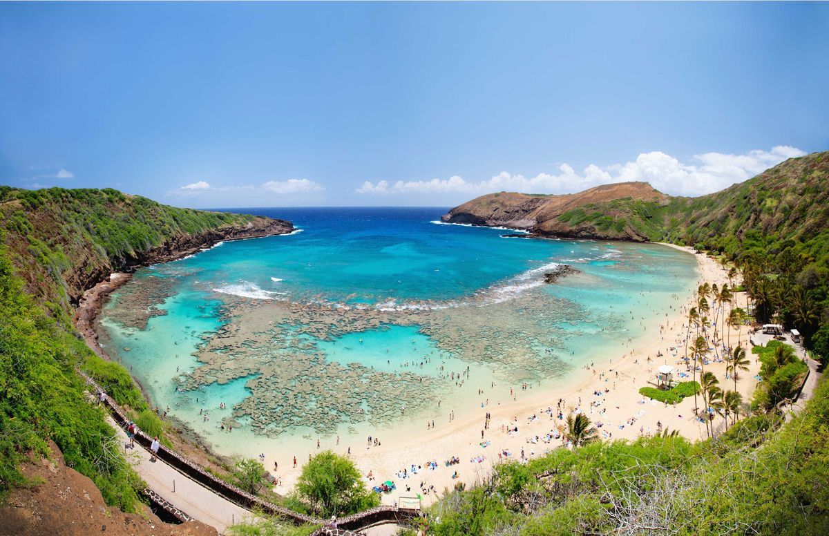 Slide 12 of 51: Hanauma BayWe couldn't leave Hawaii out because you could be taking a road trip in Hawaii! Hanauma Bay is a marine embayment formed within a tuff ring along the southeast coast of O'ahu. Explore the reefs, swim in the crystal blue waters and take in the greenery.