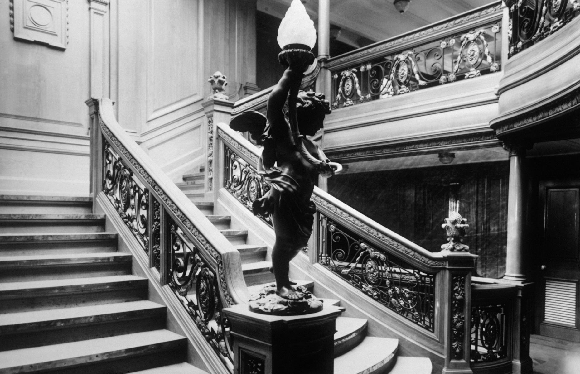 Slide 8 of 46: While at the time RMS Titanic was the largest ship afloat, the ship's appeal wasn't just her size – once onboard passengers would have been staggered by the ship's jaw-dropping interiors. The grand staircase in first class (pictured) was one of the most lavish at sea and featured a wrought-iron and glass-domed roof and oak paneling.