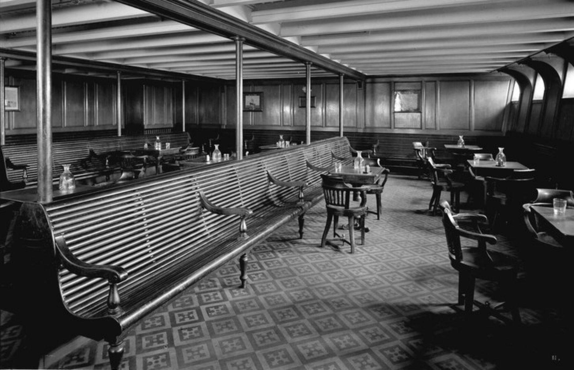 Slide 29 of 46: Third-class communal spaces had a simple, elegant feel. For example this smoking room included wooden benches and chairs, plus a tiled floor. It's likely this image is from the Olympic.