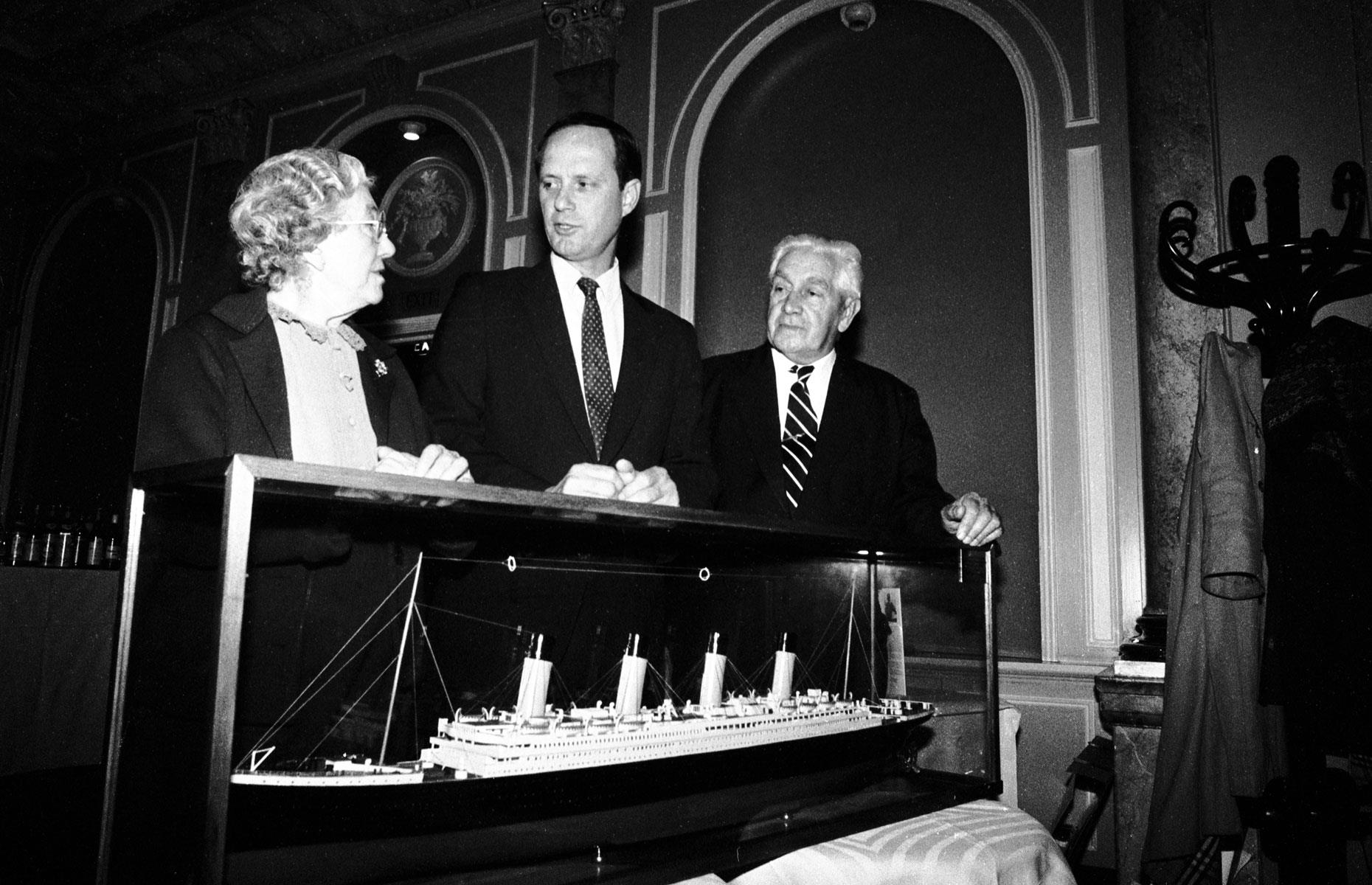 Slide 42 of 46: However, the Titanic's story didn't end with the sinking. The idea of finding the ship was first raised in 1914. But it wasn't until July 1986 that Robert Ballard (pictured center with survivors Eva Hart and Bertram Dean) discovered the wreckage of the ship. He and his team had been photographing US submarines on a secret Cold War mission, and were allowed to search for the Titanic as a side project after the main job was done.