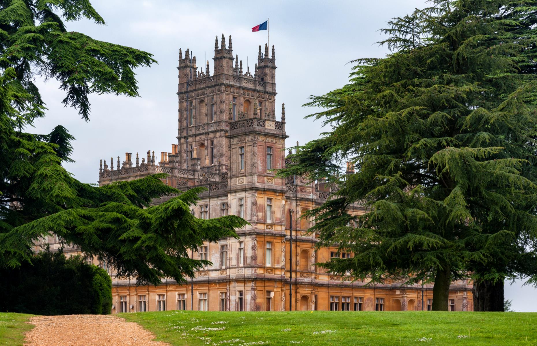 Slide 15 of 53: Downton Abbey is set in a fictional Yorkshire country estate of the same name, but of course the Jacobean Revival-style building does exist in real life. Highclere Castle, used for the exterior shots in the TV series and film, is actually close to the town of Newbury, Berkshire.
