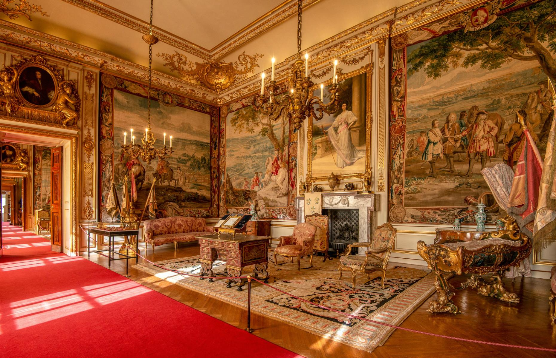 Slide 27 of 53: The palace's string of staterooms are rich in texture and detail, with tapestries and priceless portraits hanging on the walls, plush red carpets and gilded cornices. Pretty much everything is gilded, in fact, from the golden cherubs watching over the door to the golden chandeliers.