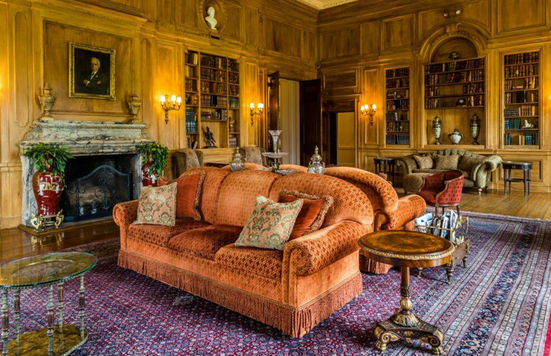 Slide 29 of 53: Even the name is fascinating – it's an acronym of Otto Hermann Kahn, the financier who built the French-style château. He used the estate as a summer home, hosting lavish parties worthy of Jay Gatsby himself in rooms such as the library, in richly decorated jewel shades.