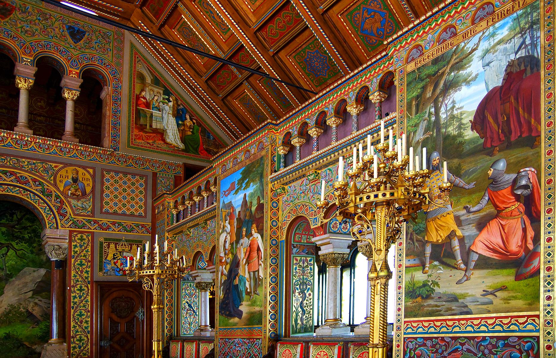 Slide 35 of 53: But the castle was also a dream world for its designer, Ludwig. Neuschwanstein's interiors display Ludwig's desire to escape into the medieval world that inspired the operas of German composer Richard Wagner. The castle is dedicated to Wagner and much of the art inside depicts the kings, poets and knights that appear in the composer's work. Discover Germany's small towns and cities here too.