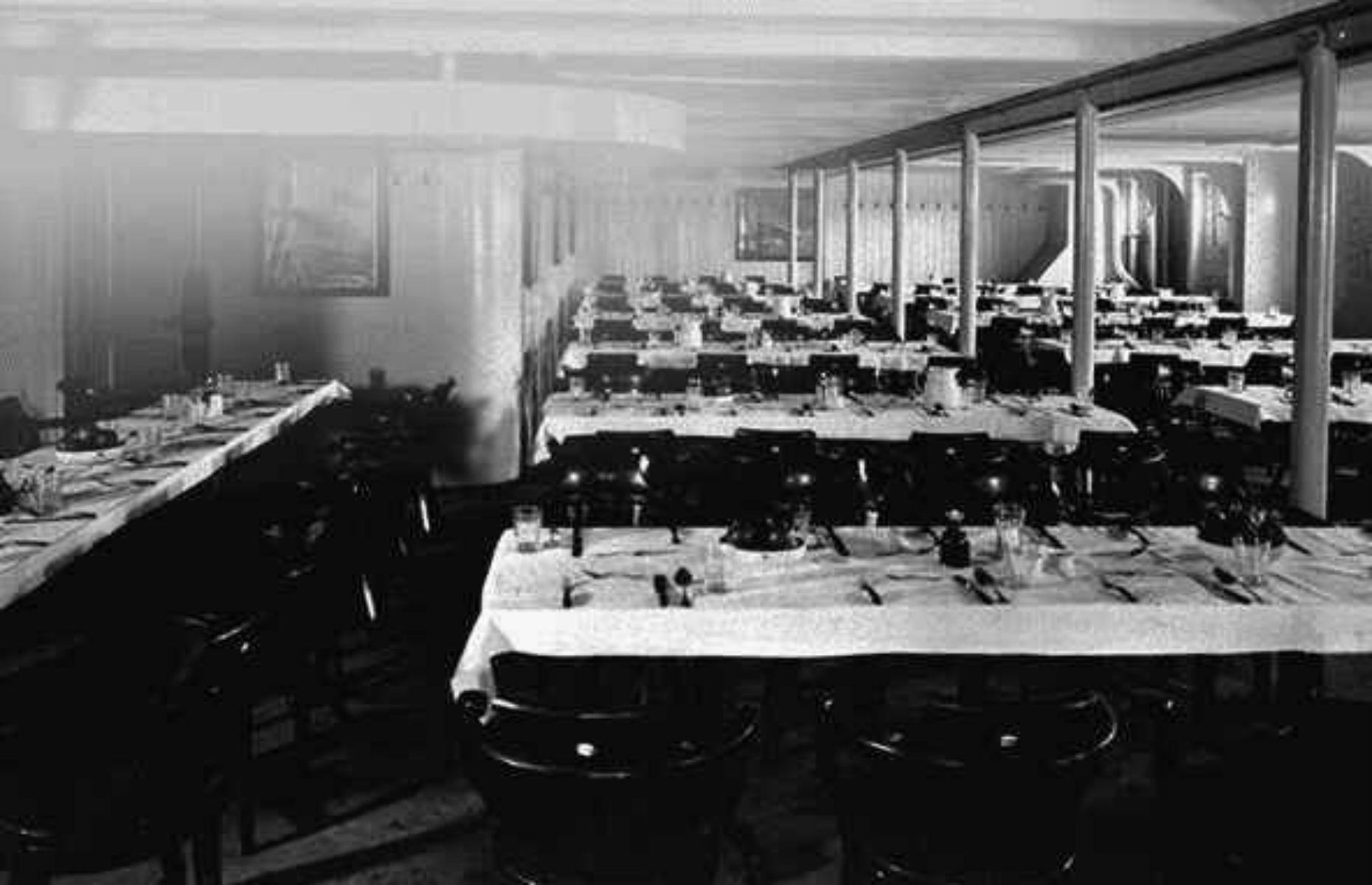 Slide 28 of 46: The dining salon had white enameled walls and tables were communal, meaning little privacy for passengers. Third class passengers weren't offered a choice of menu, but they had freshly baked bread and fruit every day. It was a huge luxury when compared with other shipping lines who usually made steerage passengers bring their own food. (Pictured is the dining room on the Olympic.)