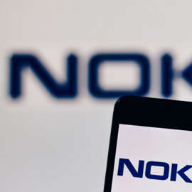 a close up of a sign: a backdrop featuring the Nokia (NOK) logo with a mobile phone featuring the Nokia logo on its screen in the foreground