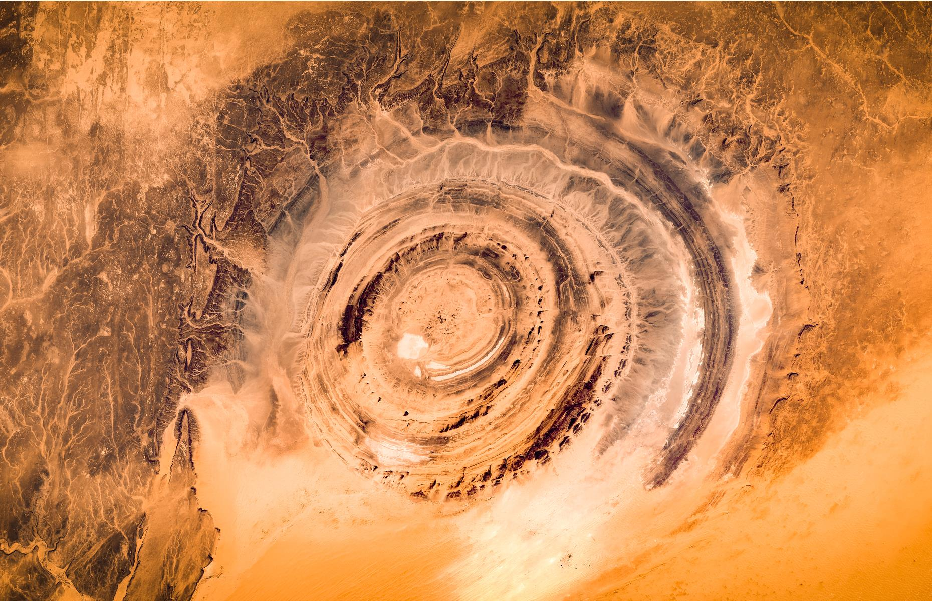 Slide 3 of 31: Astronauts have been watching the Richat Structure – also known as the Eye of Sahara – in Ouadane since humans first entered space. Viewed from the International Space Station, the 30-mile (48.2km) wide swirl resembles a bull's eye or snail's shell. The geological quirk was believed to be a crater caused by a meteorite but it's now thought it was once a dome that has eroded over time.