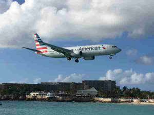 a large passenger jet flying over a body of water: American Airlines plane landing at Sint Maarten Airport (SXM) in January of 2017. (Photo by Clint Henderson/The Points Guy)