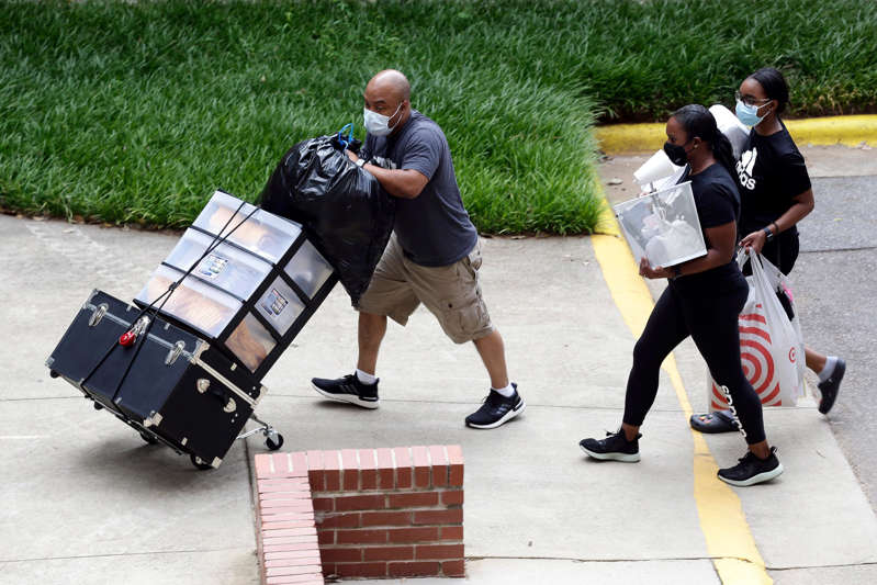 a man riding a skateboard up the side of a road: College students move in for the fall semester at North Carolina State University in Raleigh. The school announced it would close residence halls less than a week after moving classes online because of COVID-19.