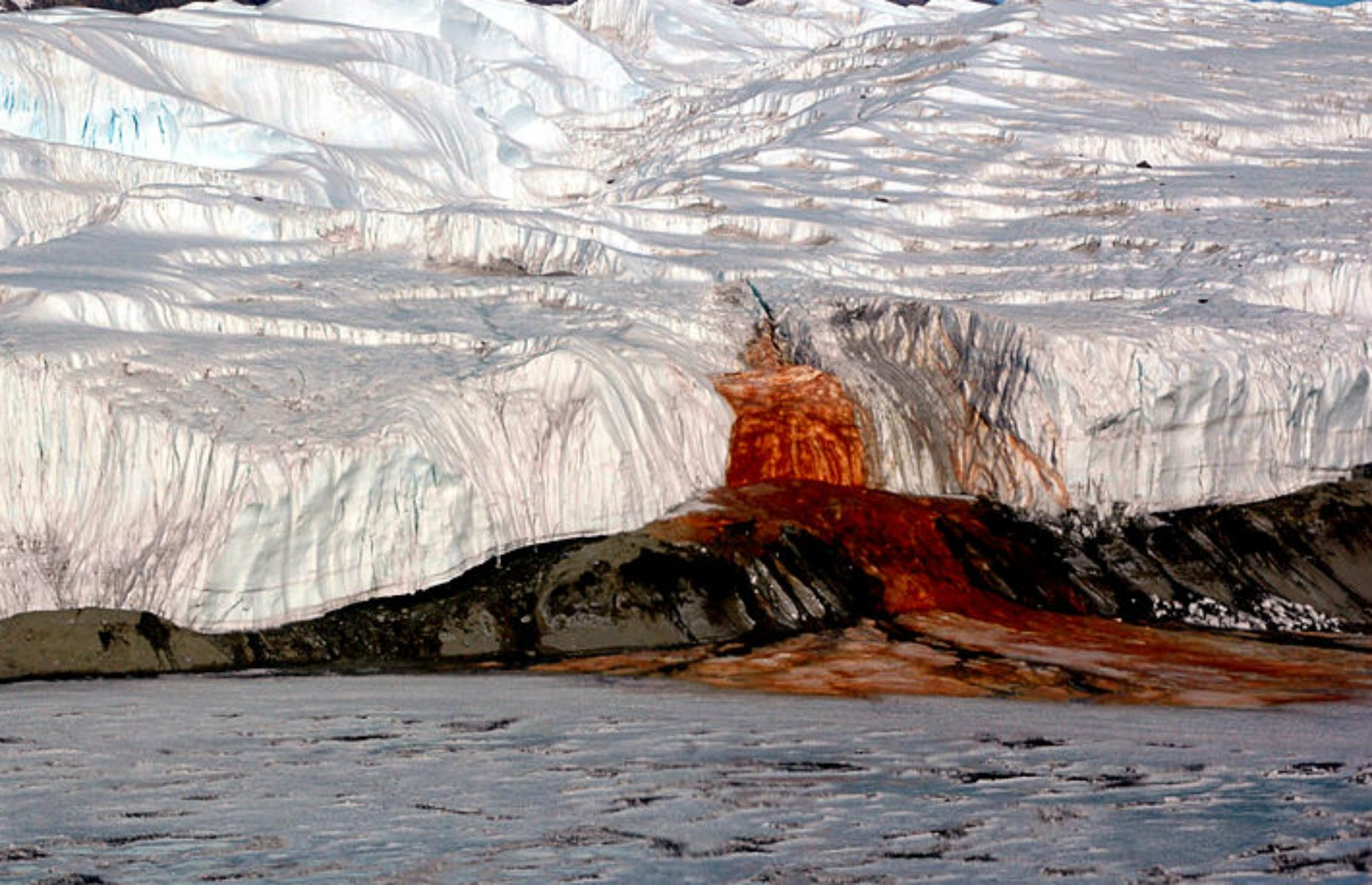 Slide 8 of 31: The world's coldest and perhaps most enigmatic continent is home to a blood-red waterfall that seeps into the ice. Geologists originally thought the red color was due to algae but the truth is actually much more interesting. It started around two million years ago when a saltwater pool was trapped inside Taylor Glacier. The sealed, airless lake's high iron content and salinity caused the rust-red color that eventually oozed out of a fissure in the ice.