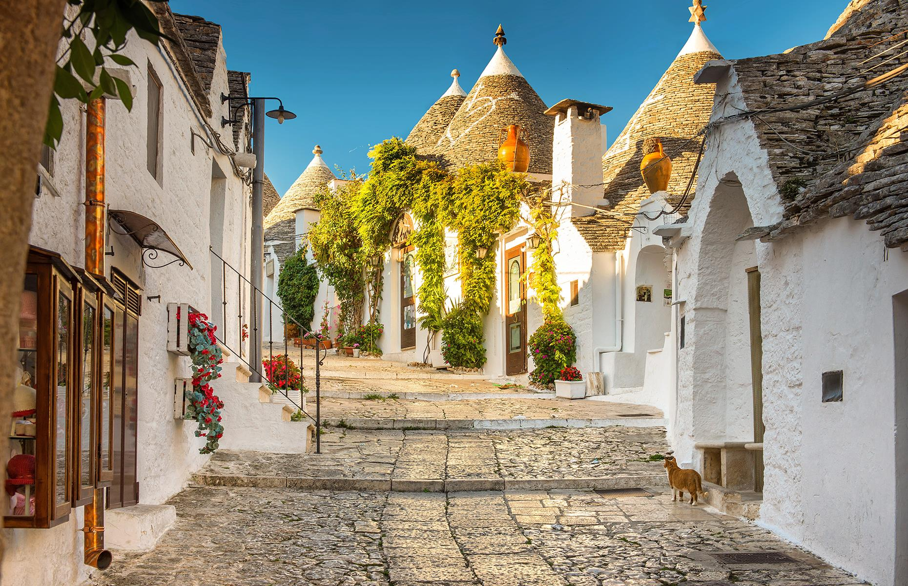 Slide 9 of 31: It's simply impossible not to find a picture-perfect street in Alberobello, a UNESCO World Heritage Site in its entirety. The small town in Italy's heel – Puglia – is famous for its unusual trulli homes, built from white-washed local limestone, with a characteristic conical rooves. The prettiest streets are in the historical heart of the town. Rione Monti is the more commercialized side with plenty of hotels, restaurants and shops, while Rione Aia Piccola is much quieter and still largely residential.