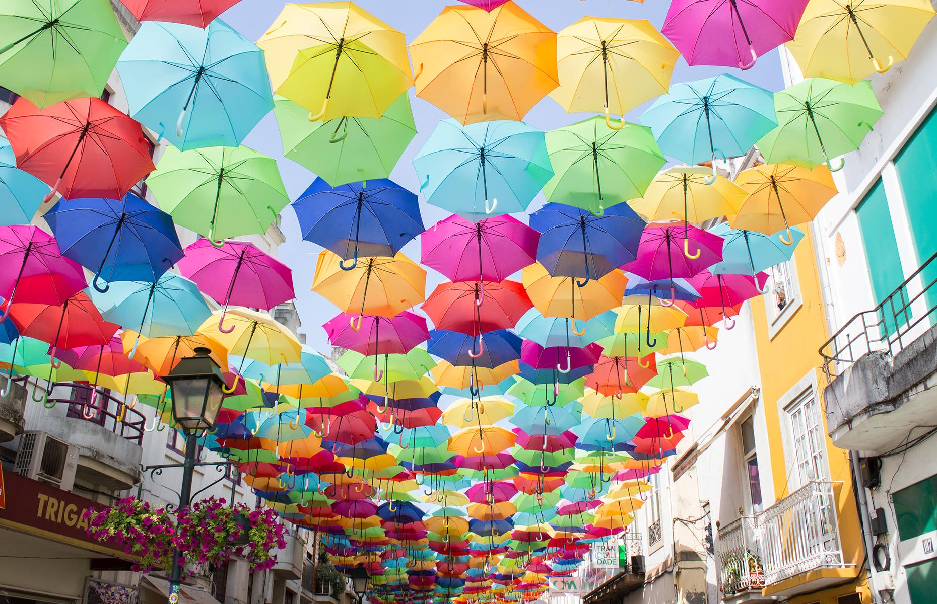 Slide 26 of 31: What began in 2011 as an art installation for Águeda's annual art festival has turned into the city's most famous attraction. Today, four of Águeda's streets are turned into a colorful spectacle with the help of more than 3,000 umbrellas, usually attracting thousands of tourists.