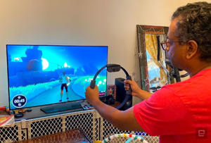 a man standing in front of a television: Nintendo Ring Fit Adventure