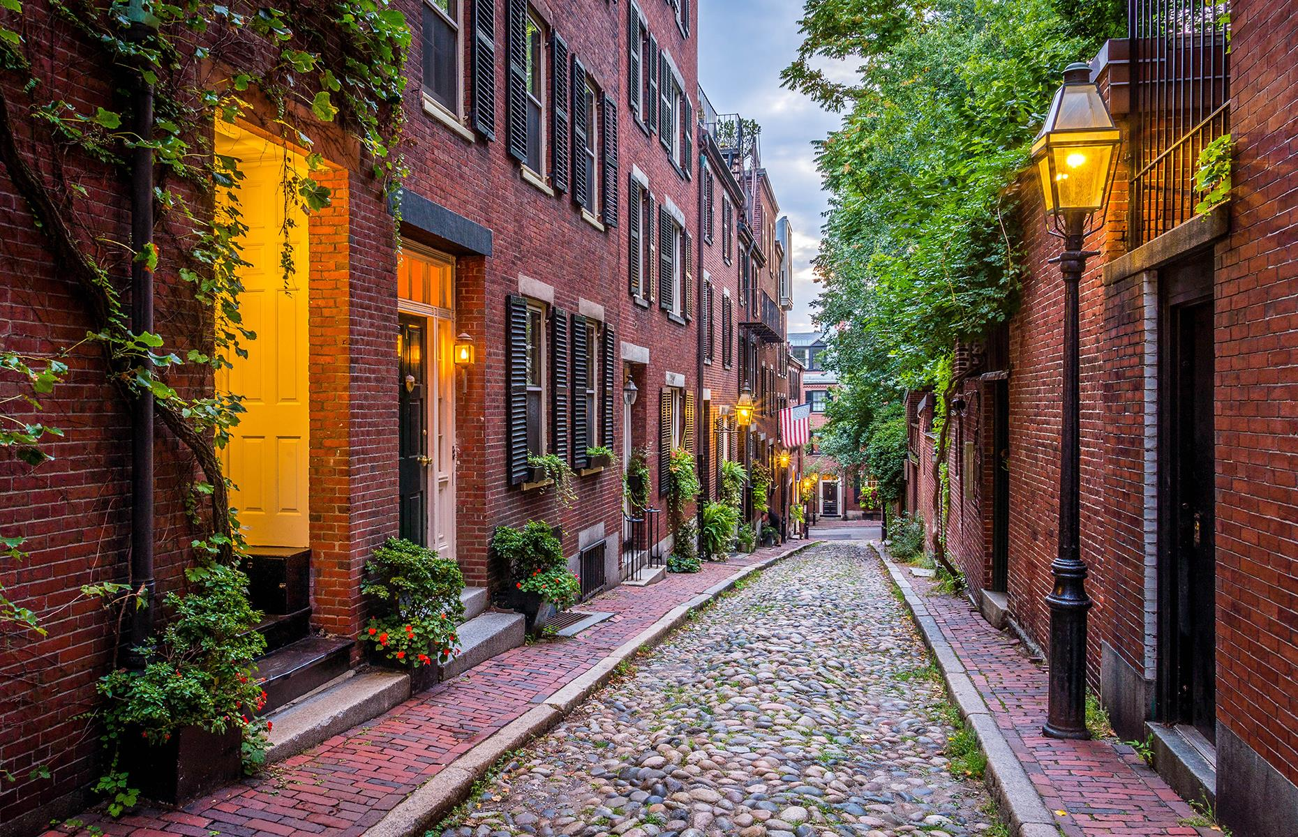 Slide 2 of 31: Located in Boston's historic Beacon Hill neighborhood, Acorn Street is often said to be the most photographed street in the US. Wealthy tradesmen and artists lived here in the 19th century, and today it's one of Boston's most famous attractions, instantly recognizable thanks to its Federal-style brick rowhouses and gas lanterns.