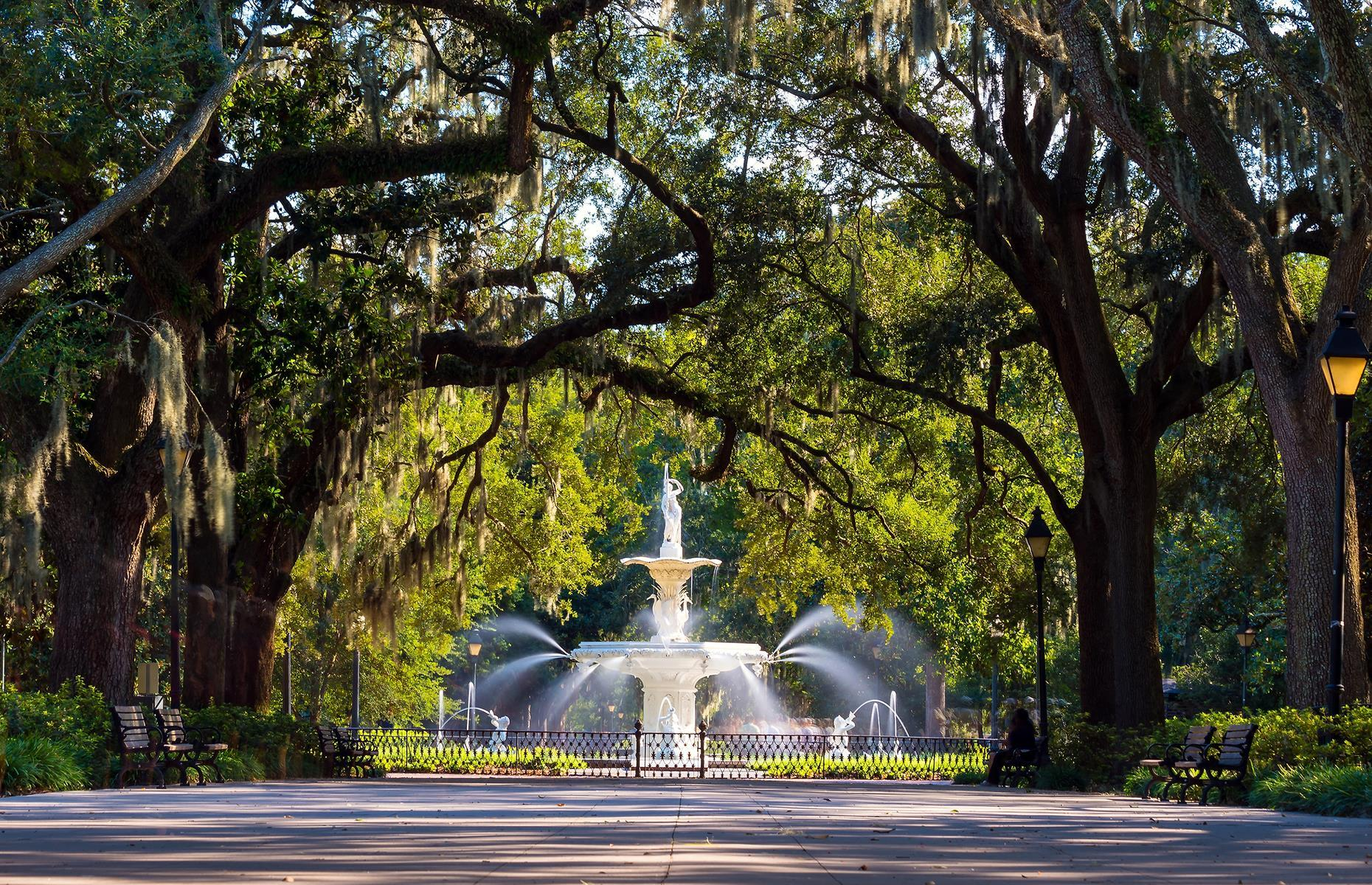 Slide 20 of 41: Savannah's historic center is one the largest National Historic Landmark districts in the country, and pretty Forsyth Fountain is at its heart. With its canopies of ancient oak trees, bearded with Spanish moss, Forsyth Park is a stunning urban green space. However there's also no escaping the Georgian city's past which is inextricably linked with slavery – the grand old homes tell of wealth acquired through an enslaved workforce's cultivation of cotton and rice.