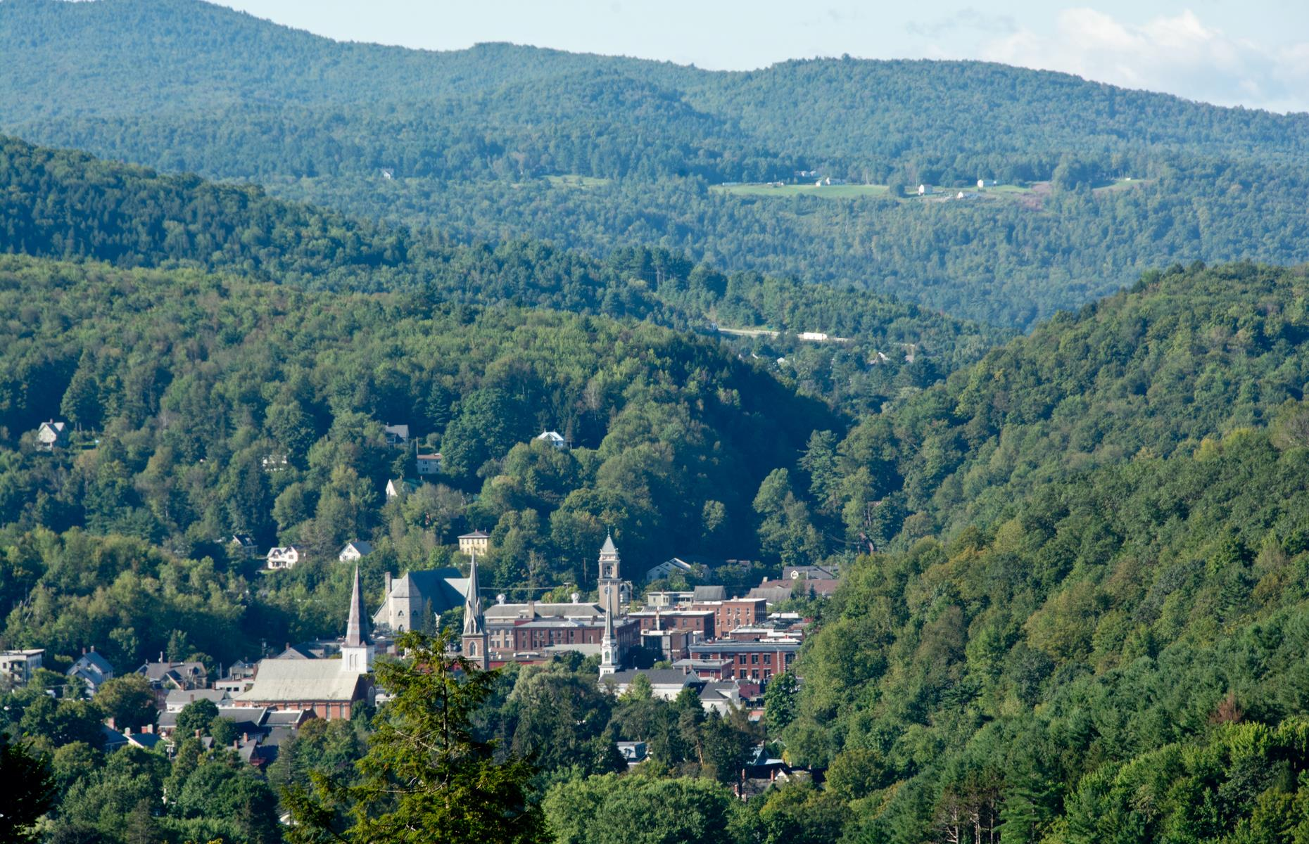 Slide 6 of 41: Proudly known as the tiniest of all state capitals, Montpelier is mostly associated with maple syrup and mountains but it's got plenty of history too. Snug in the foothills of the Green Mountains, its downtown area is the largest National Register of Historic Places District in Vermont. Today the 19th-century buildings are filled with quaint stores including vintage record and independent bookshops, and historic inns. Its skyline is dotted with church steeples and dominated by its grand gold-domed State House.